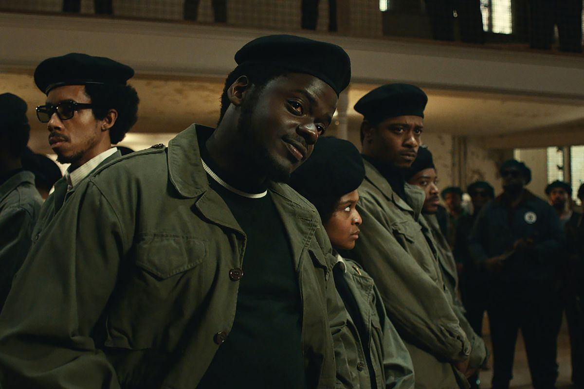 Daniel Kaluuya stands in the center of a group of Black Panther Party members.