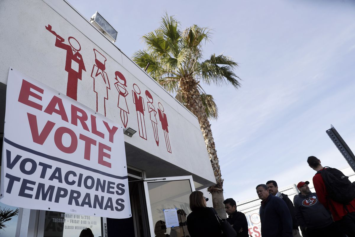 """Voters line up outside a building that sports a banner reading """"Early Vote / Votaciones Tempranas."""""""