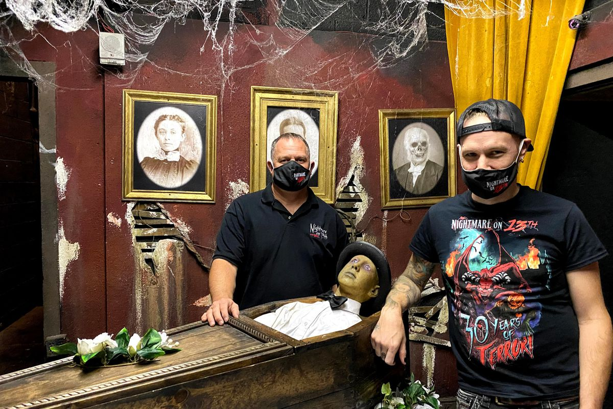 Mike Henrie, owner, left, and Jimmy Dilley, art and cast director of Nightmare on 13th, pose with a longtime resident of the haunted house.