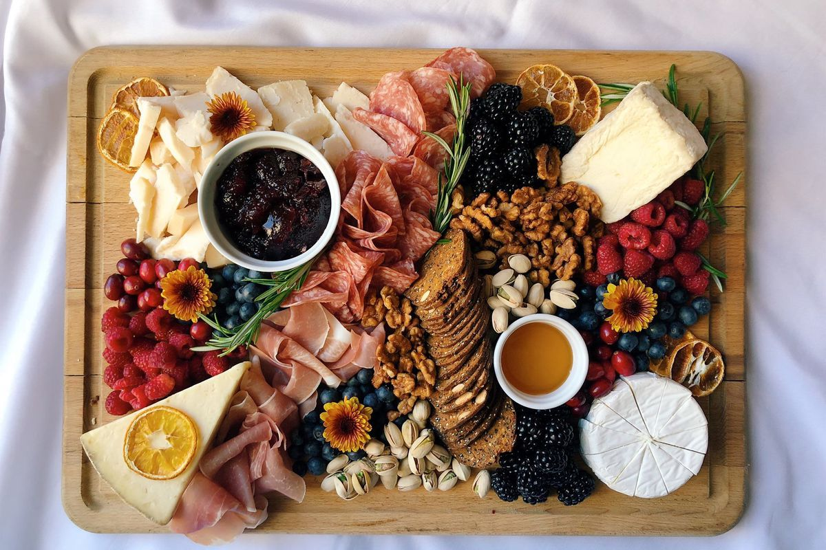 A rectangular wooden board covered with cheese, meat and berries