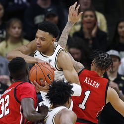 Colorado guard Tyler Bey, center, pulls in a rebound between Utah center Lahat Thioune, left, and forward Timmy Allen in the second half of an NCAA college basketball game Sunday, Jan. 12, 2020, in Boulder, Colo.