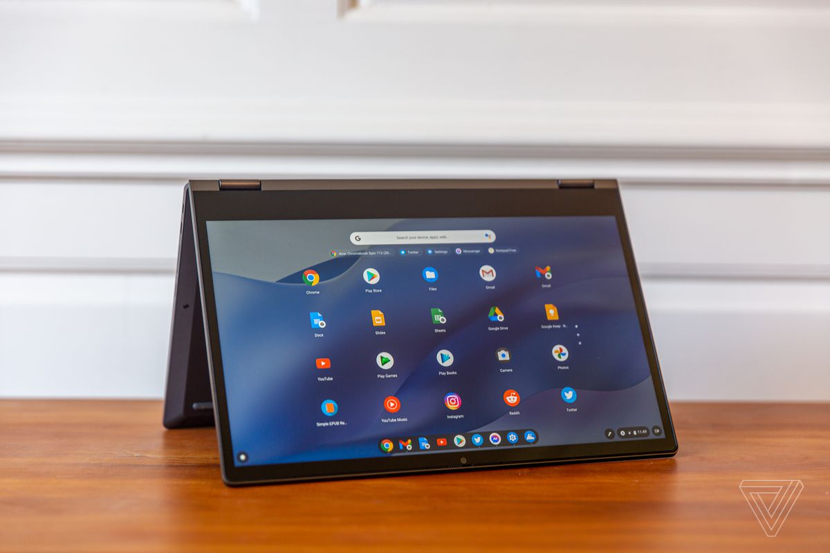 The Lenovo Flex 5 Chromebook in tent mode, angled to the right. The screen displays a grid of Chrome OS apps on a blue wavy background.