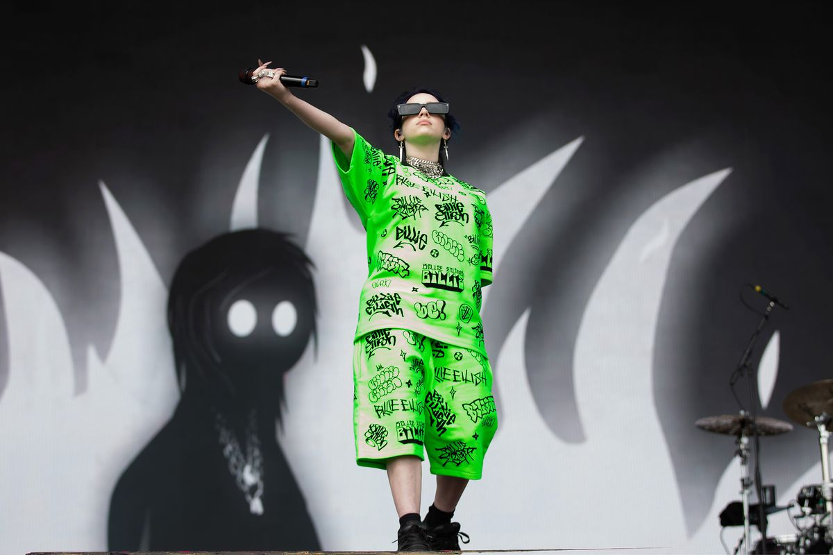 Billie Eilish stands onstage in front of a backdrop of greyscale flames and a white-eyed shillouette, holding a microphone outstretched towards the crowd