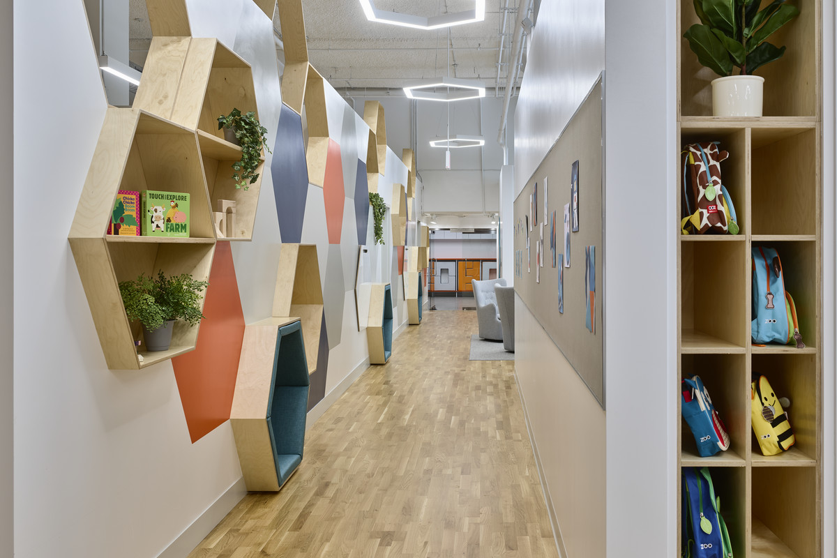 A light-filled interior of a daycare, populated with cubbies, plants, and children's books