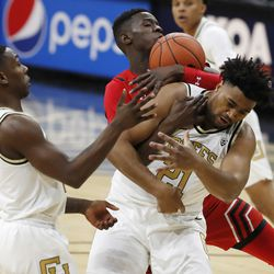 Utah center Lahat Thioune, back, wrestles away a rebound from Colorado forward Evan Battey, front right, as Colorado guard McKinley Wright IV, left, looks on in the first half of an NCAA college basketball game Sunday, Jan. 12, 2020, in Boulder, Colo.
