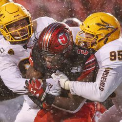 Utah Utes running back Zack Moss (2) is wrapped up at the line of scrimmage by Arizona State Sun Devils defensive linemen Roe Wilkins (95) and Jermayne Lole (90) during the second half of an NCAA football game at Rice-Eccles Stadium in Salt Lake City on Saturday, Oct. 19, 2019.