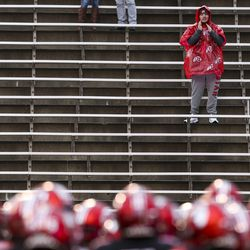 A Utah Utes fan cheers as the team huddles up during warmups before the start of an NCAA football game between the Utah Utes and Arizona State Sun Devils at Rice-Eccles Stadium in Salt Lake City on Saturday, Oct. 19, 2019.