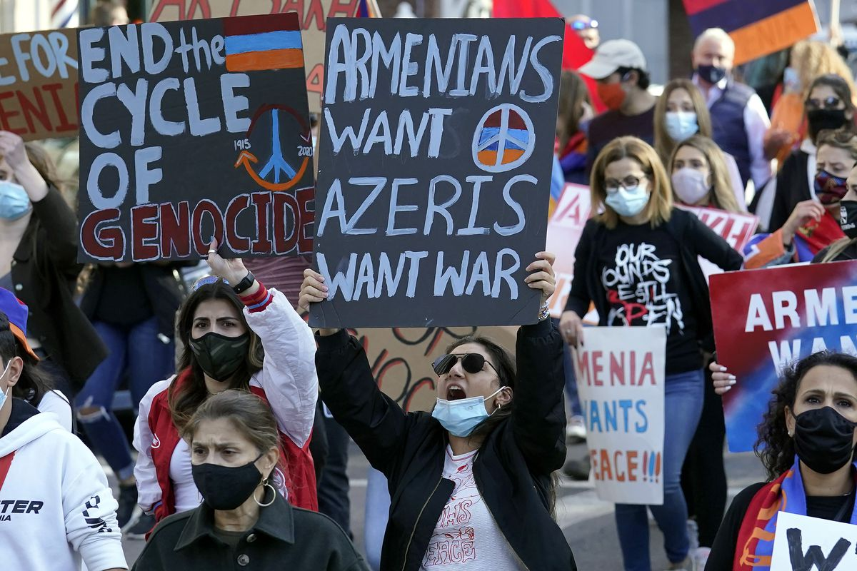 Pro-Armenian protesters display placards while calling for an end to hostilities in Nagorno-Karabakh, also known as Artsakh, during a demonstration, Sunday, Oct. 11, 2020, in Boston. The latest outburst of fighting between Azerbaijani and Armenian forces began Sept. 27, 2020, and marked the biggest escalation of the decades-old conflict over Nagorno-Karabakh.