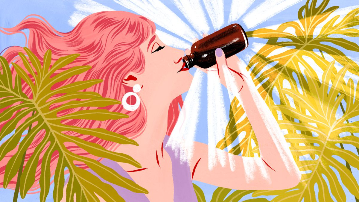 A woman with red hair drinks out of a brown bottle glowing with wellness