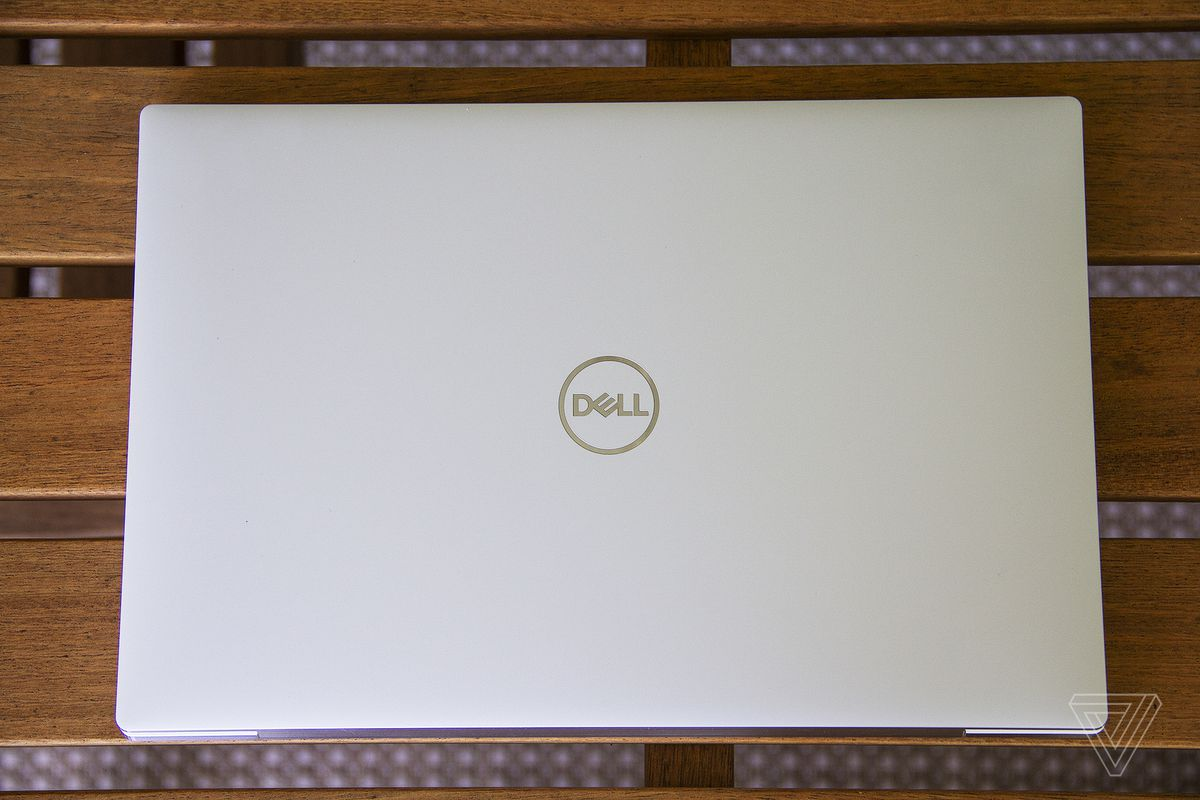The Dell XPS 13 OLED lid on a wooden table seen from the top.