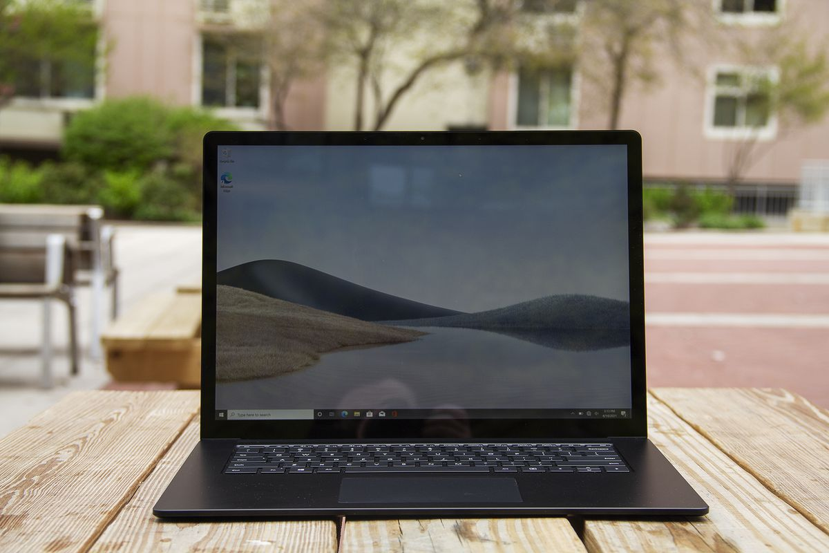 The Surface Laptop 4 15-inch open on a picnic table with a pink apartment building in the background. The screen displays sand dunes with a blue sky.