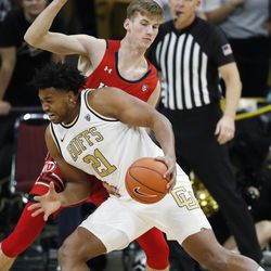 Colorado forward Evan Battey, front, drives to the basket as Utah center Branden Carlson defends in the first half of an NCAA college basketball game Sunday, Jan. 12, 2020, in Boulder, Colo.