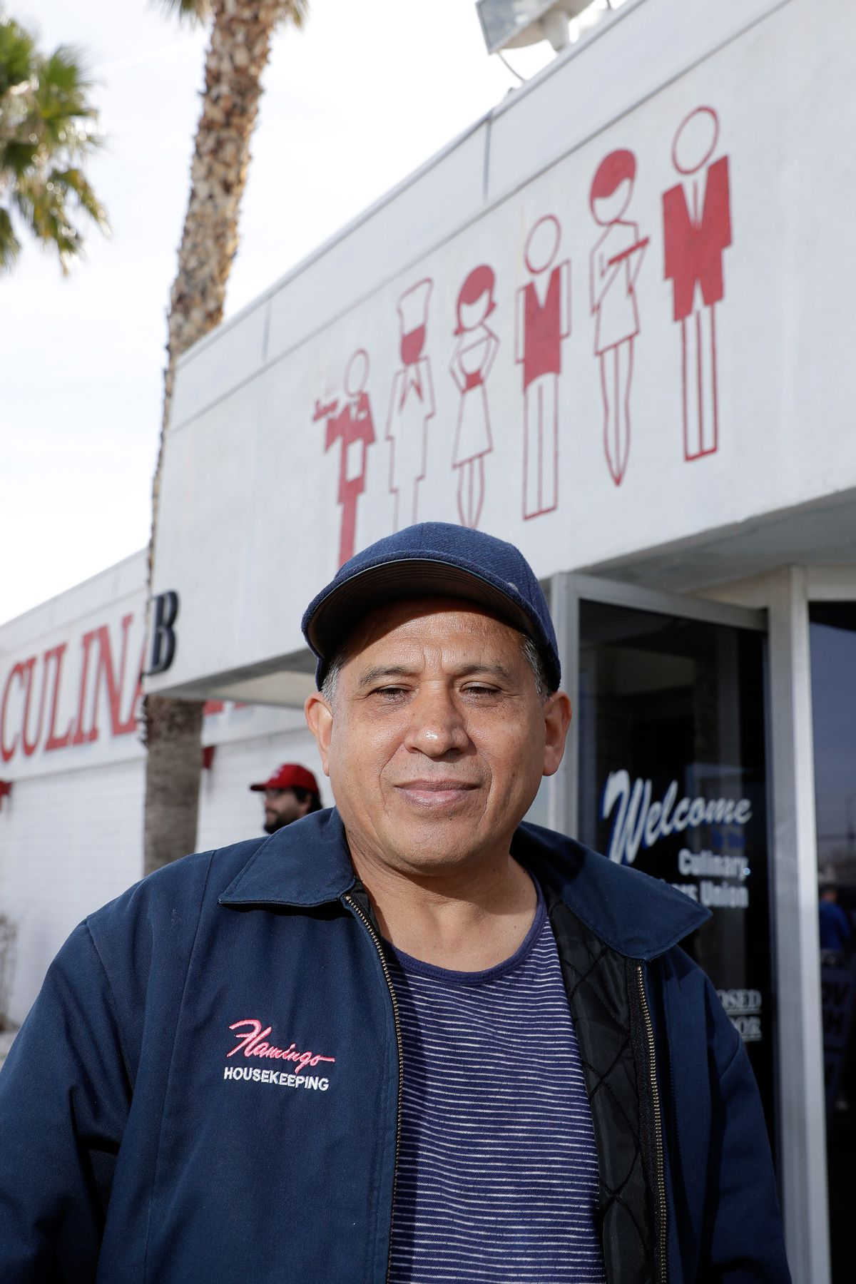 """A man wearing a blue cap and a blue jacket with the logo """"Flamingo housekeeping"""" stands in front of the Culinary Union hall."""
