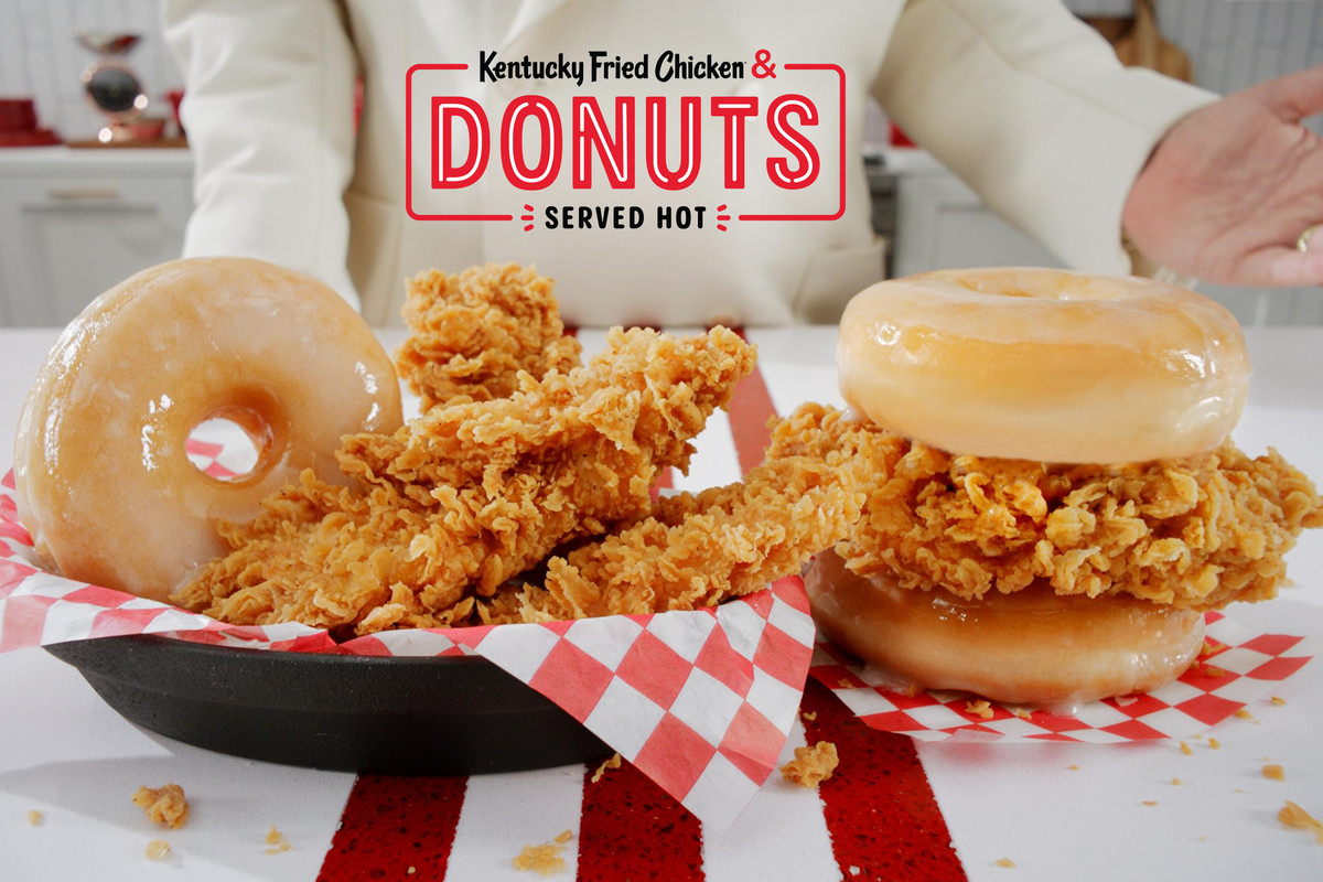 """A basket of fried chicken with a glazed donut, and a piece of fried chicken in between two glazed donuts, on a table under a sign reading """"kentucky fried chicken & donuts served hot"""""""