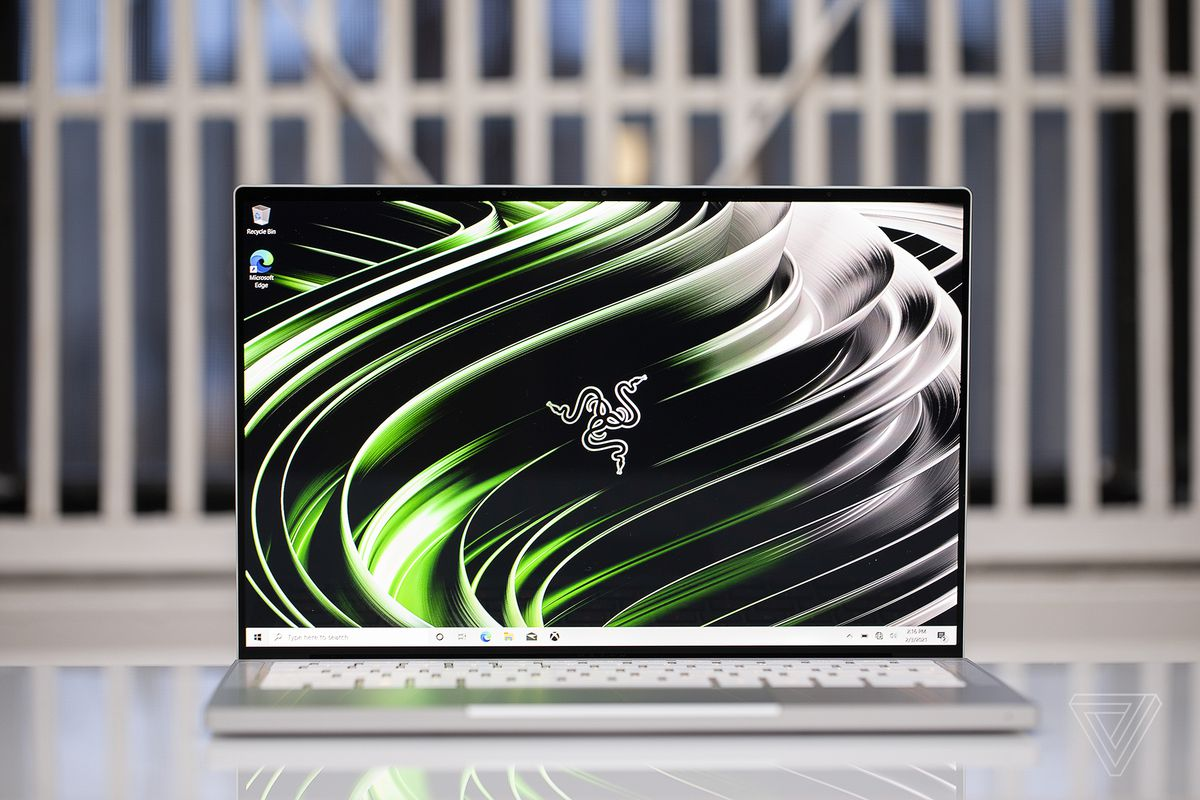 The Razer Book 13 open. The screen displays the Razer logo on a green and black background.