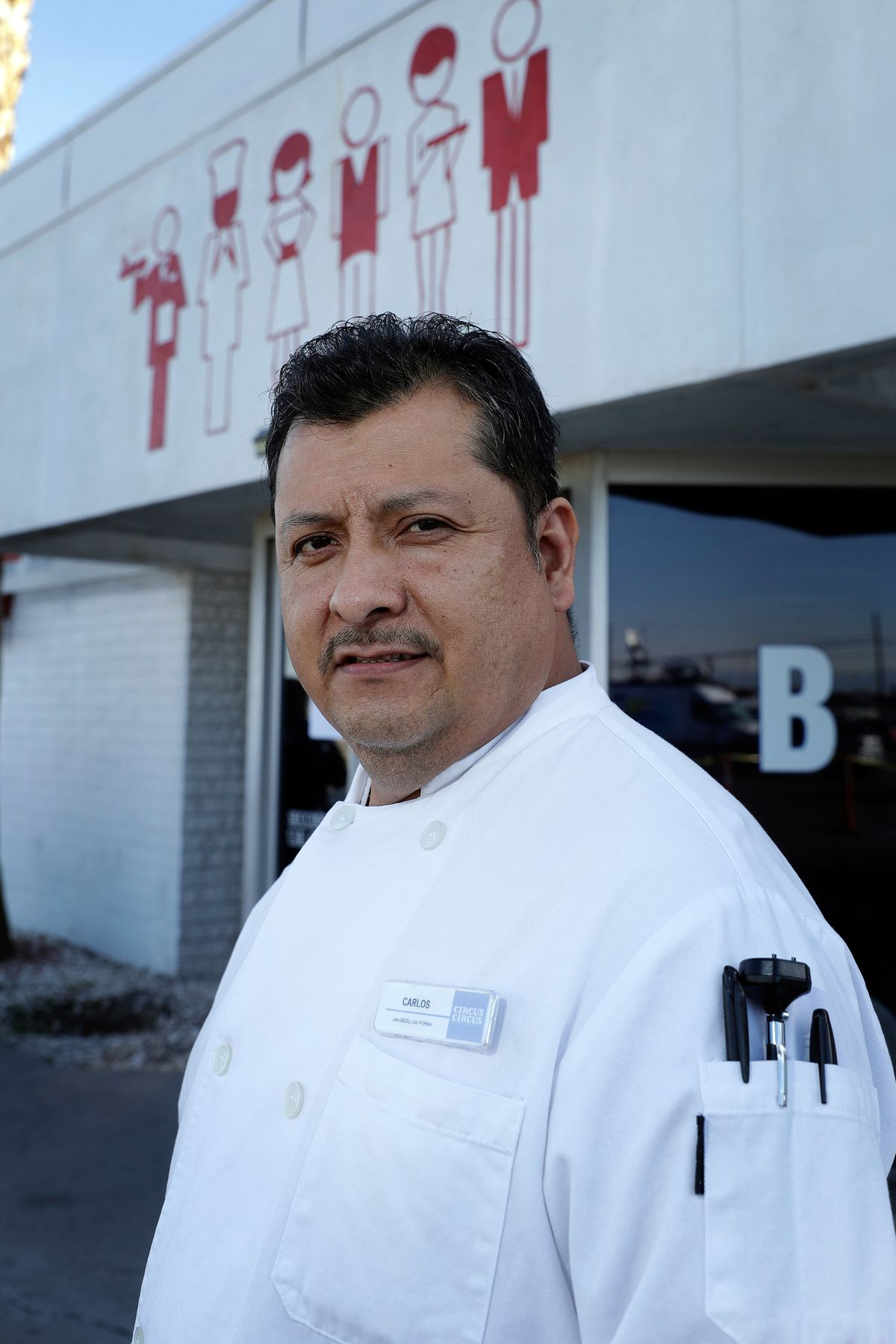 A man in a chef's coat looks into the camera.
