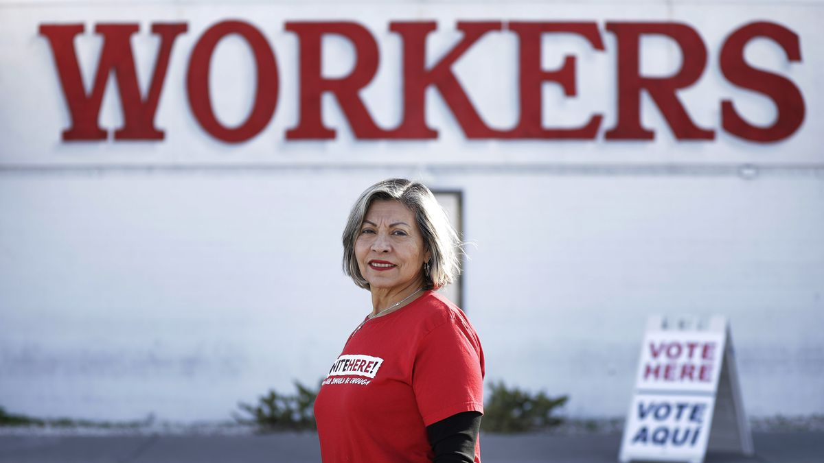 """A woman with gray hair and a red t-shirt reading """"Vote Here"""" stands in front of a """"Workers"""" sign."""