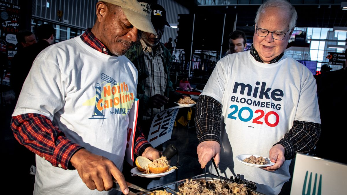 Two men wearing Mike Bloomberg t-shirts take food from a buffett.
