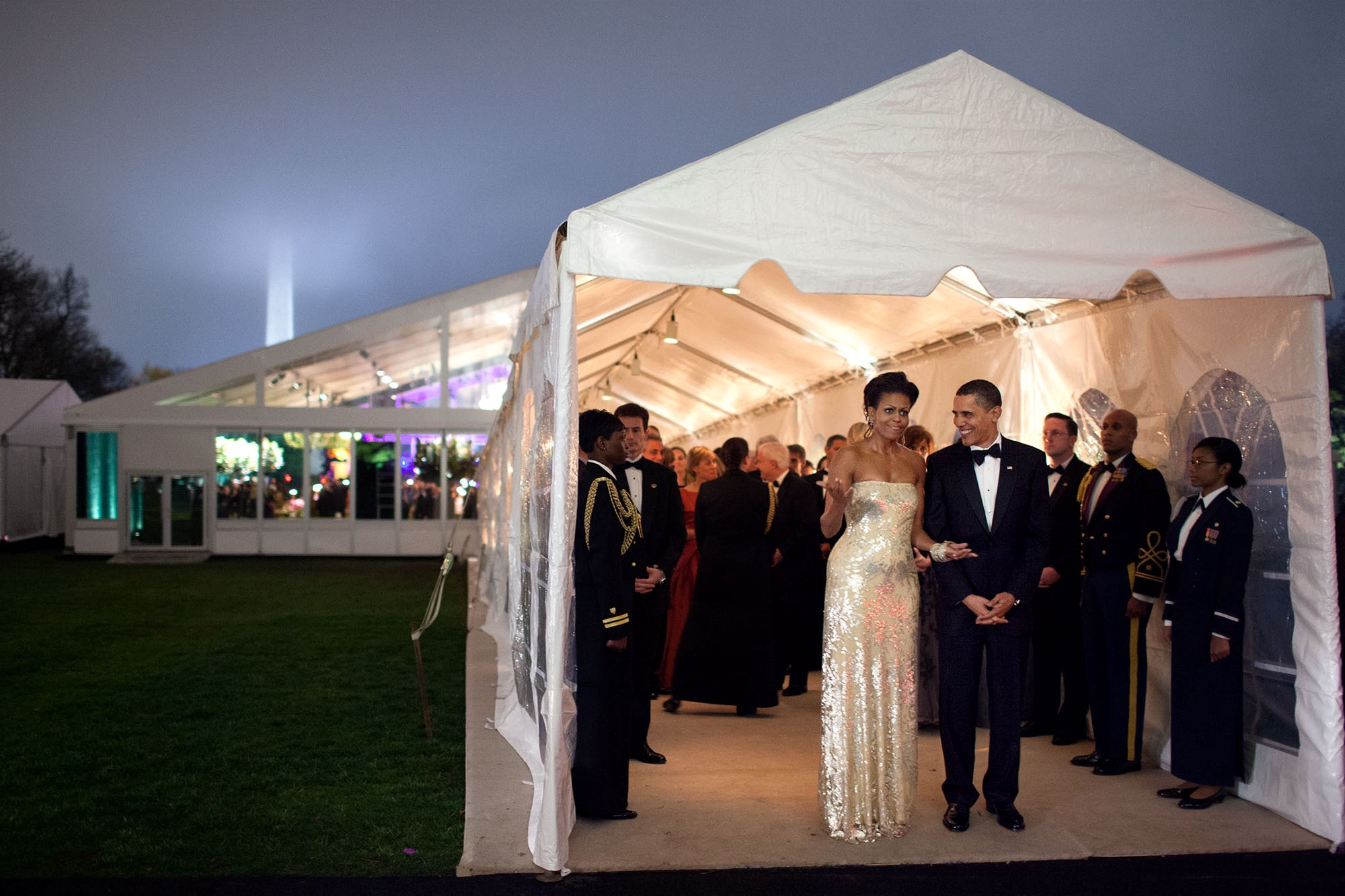 Barack and Michelle Obama stand at the entrance to a large white tent on the White House South Lawn