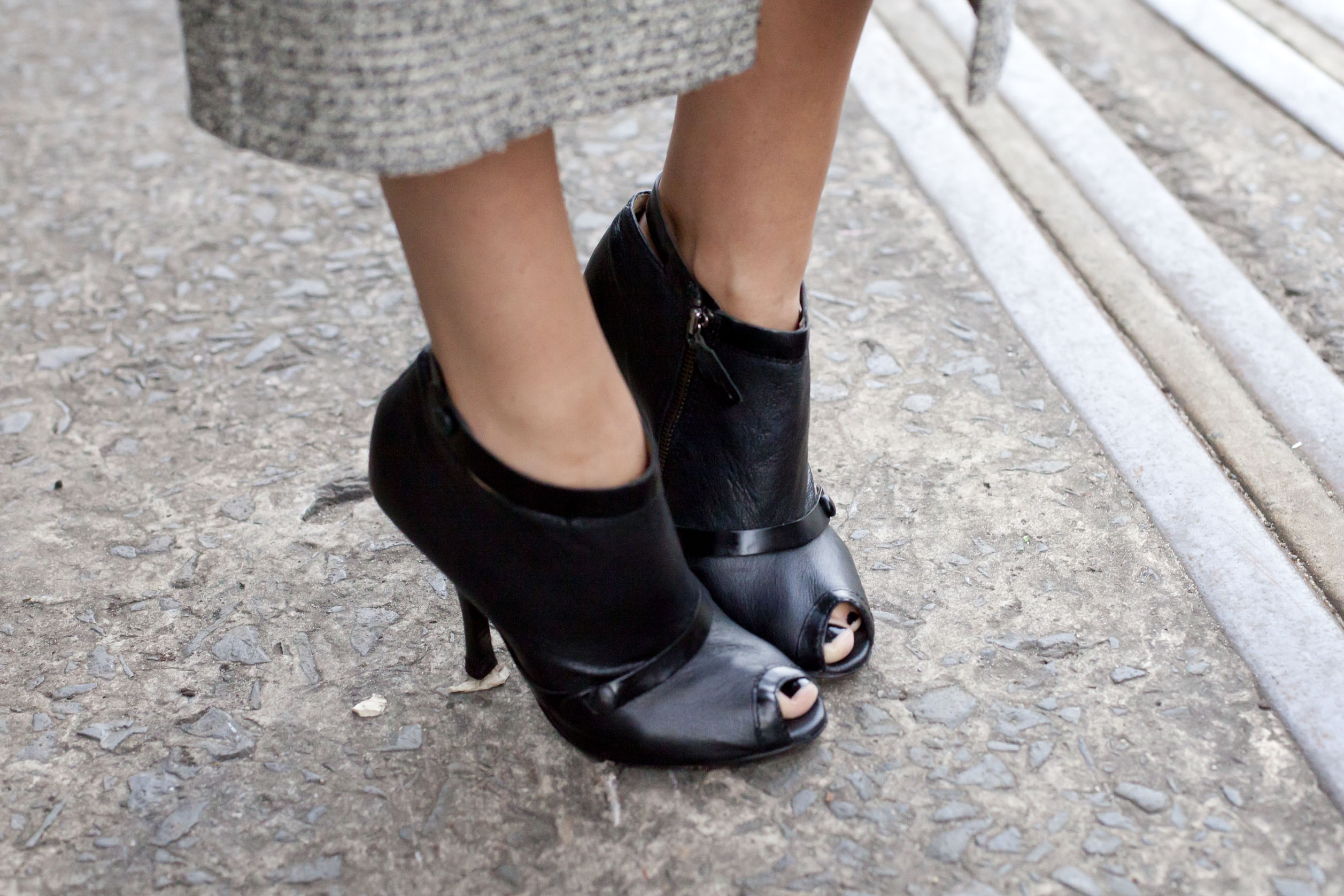 A woman from the shins down wearing black open-toe high heel boots.