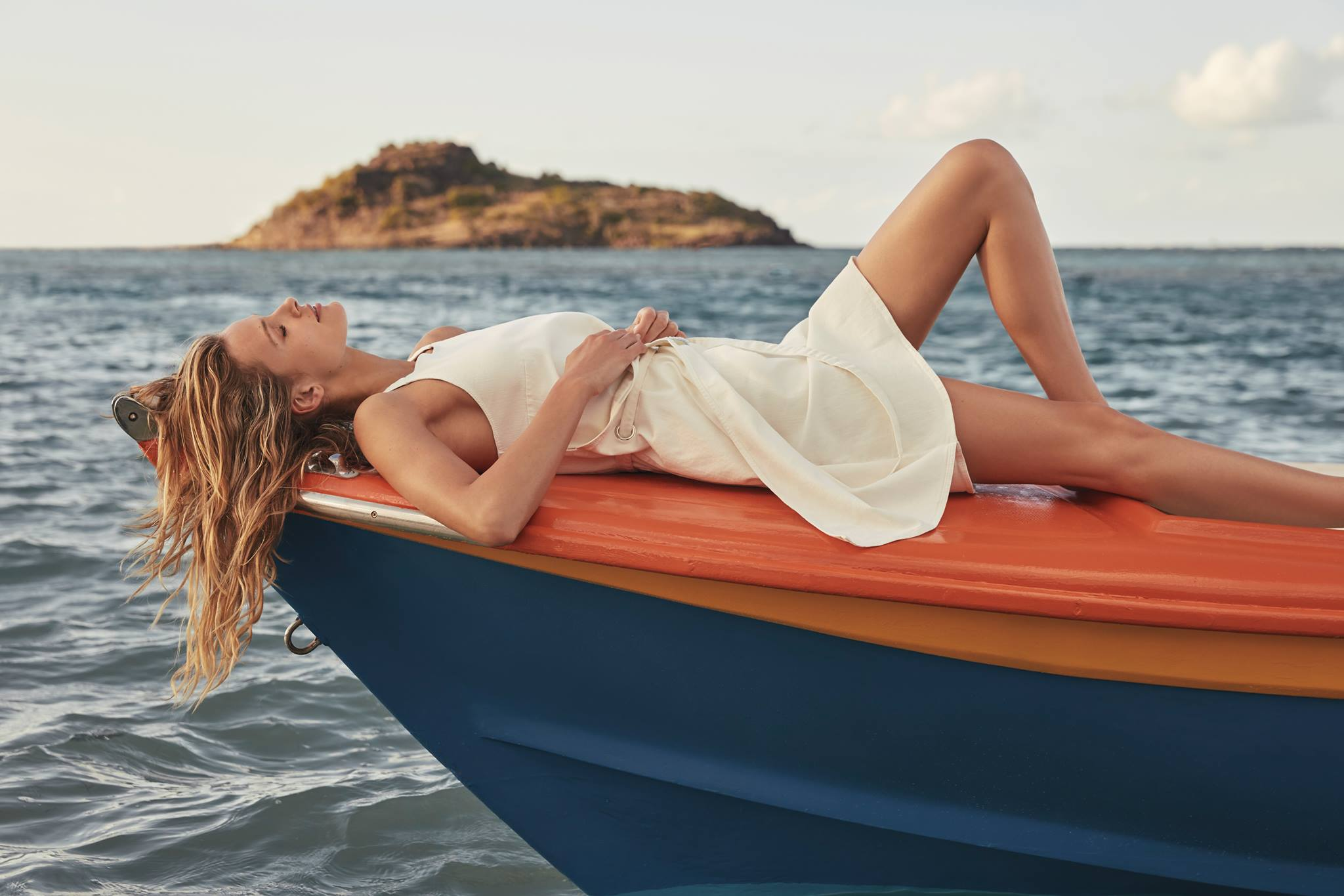 A woman in a white dress on a boat at sea.