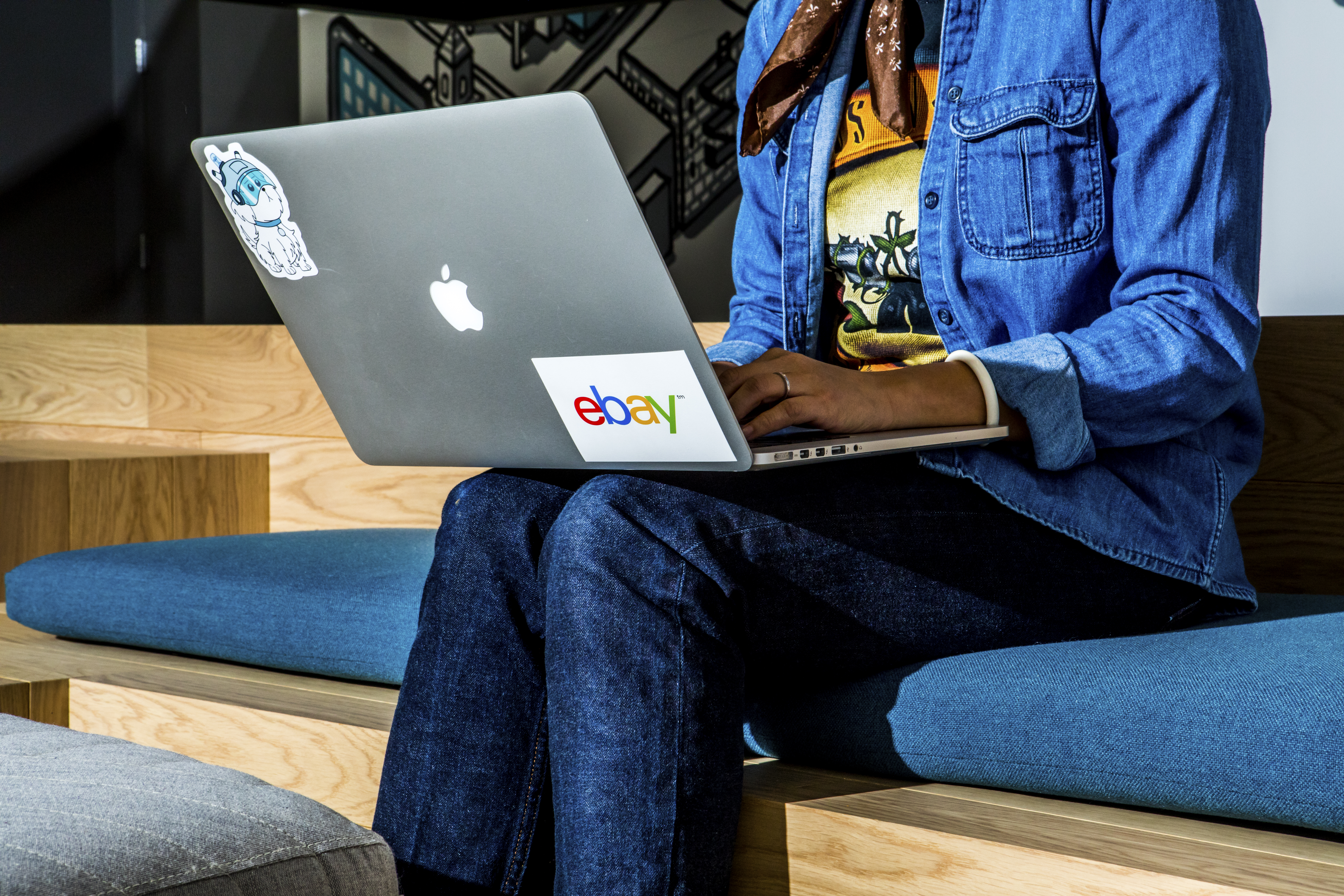 Woman sits with laptop on her lap. The laptop has an eBay sticker.