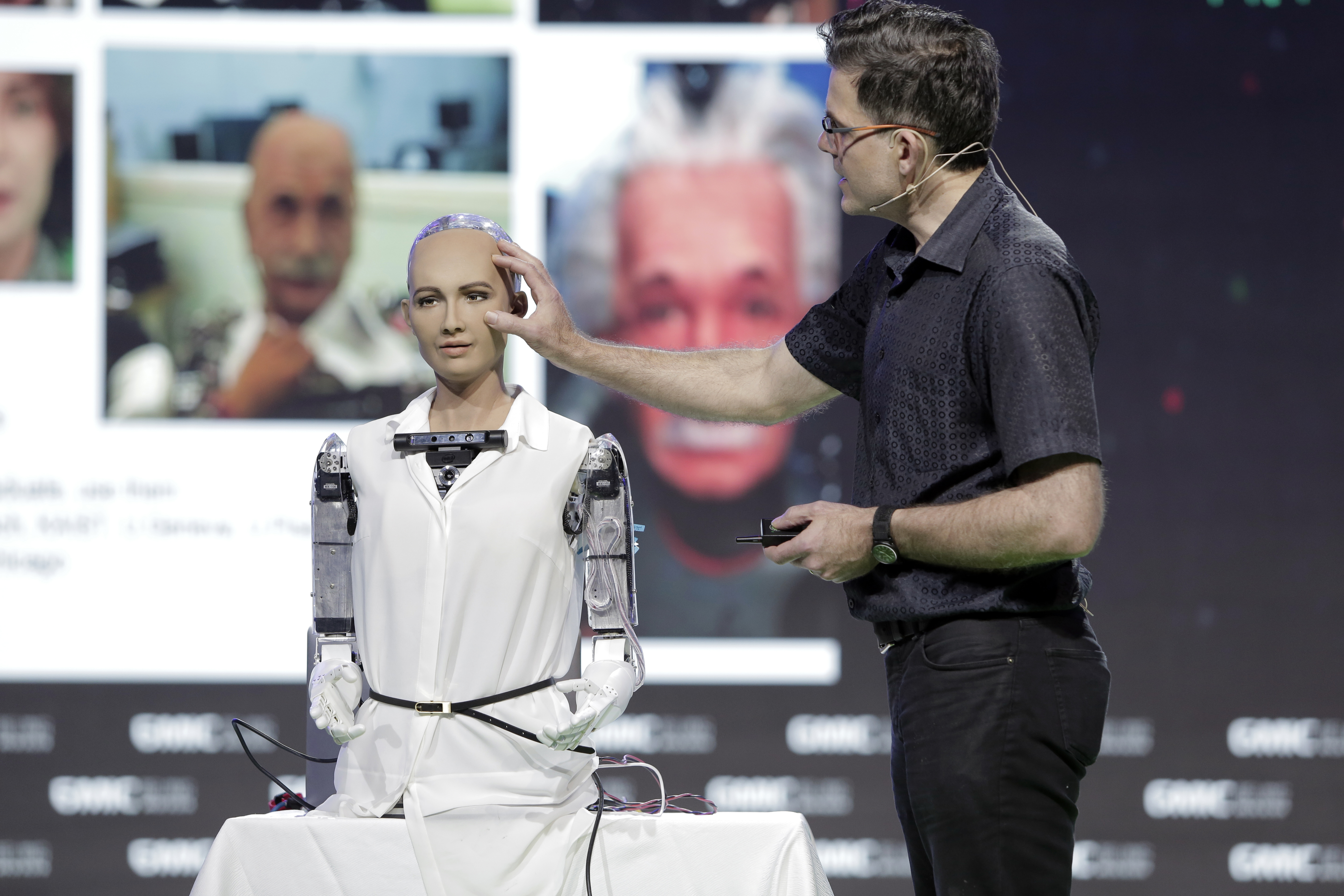A man on stage with a female-presenting robot with no hair and a white belted button down.
