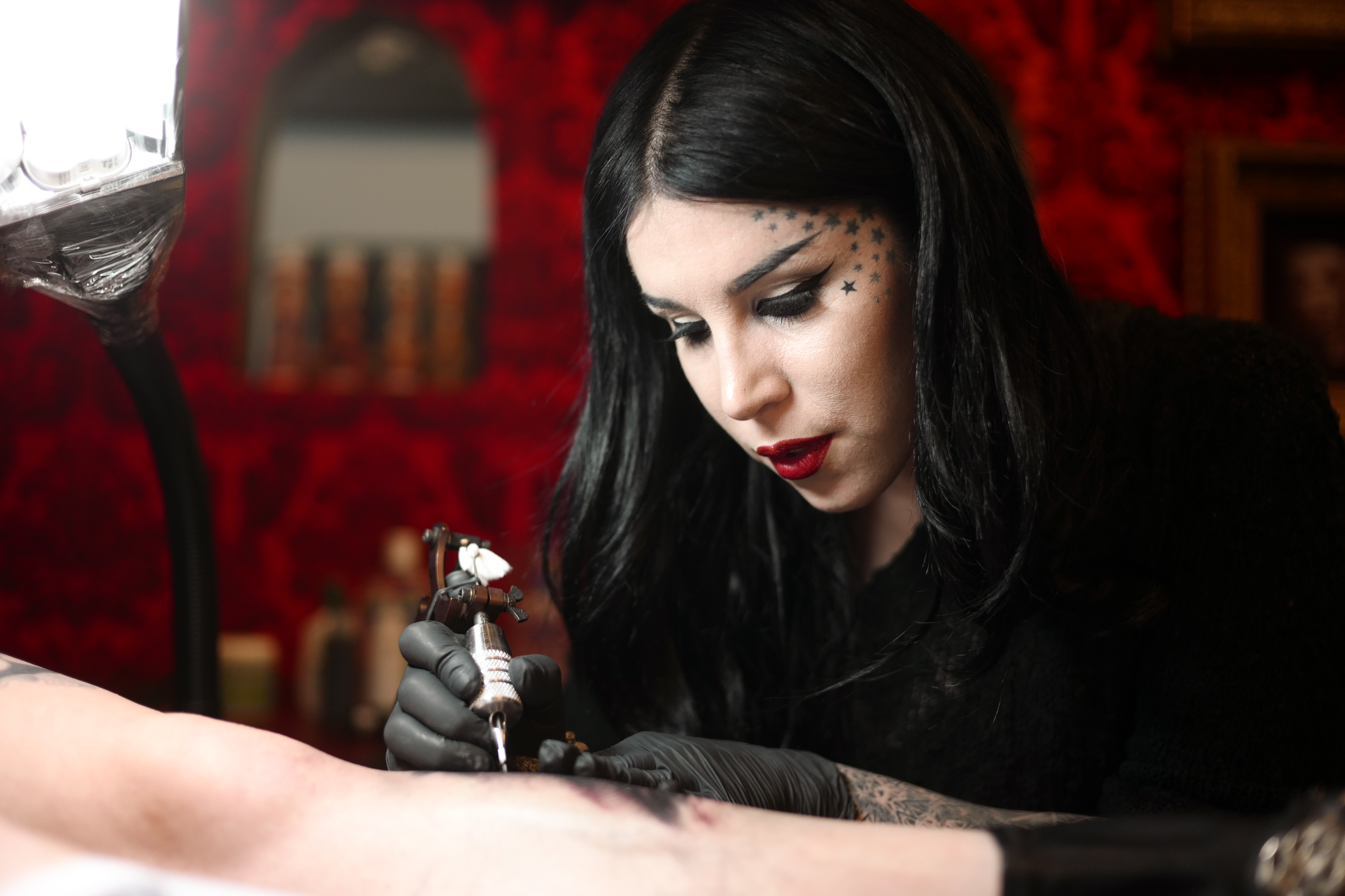 Kat Von D tattoos a person's arm at her West Hollywood tattoo studio.