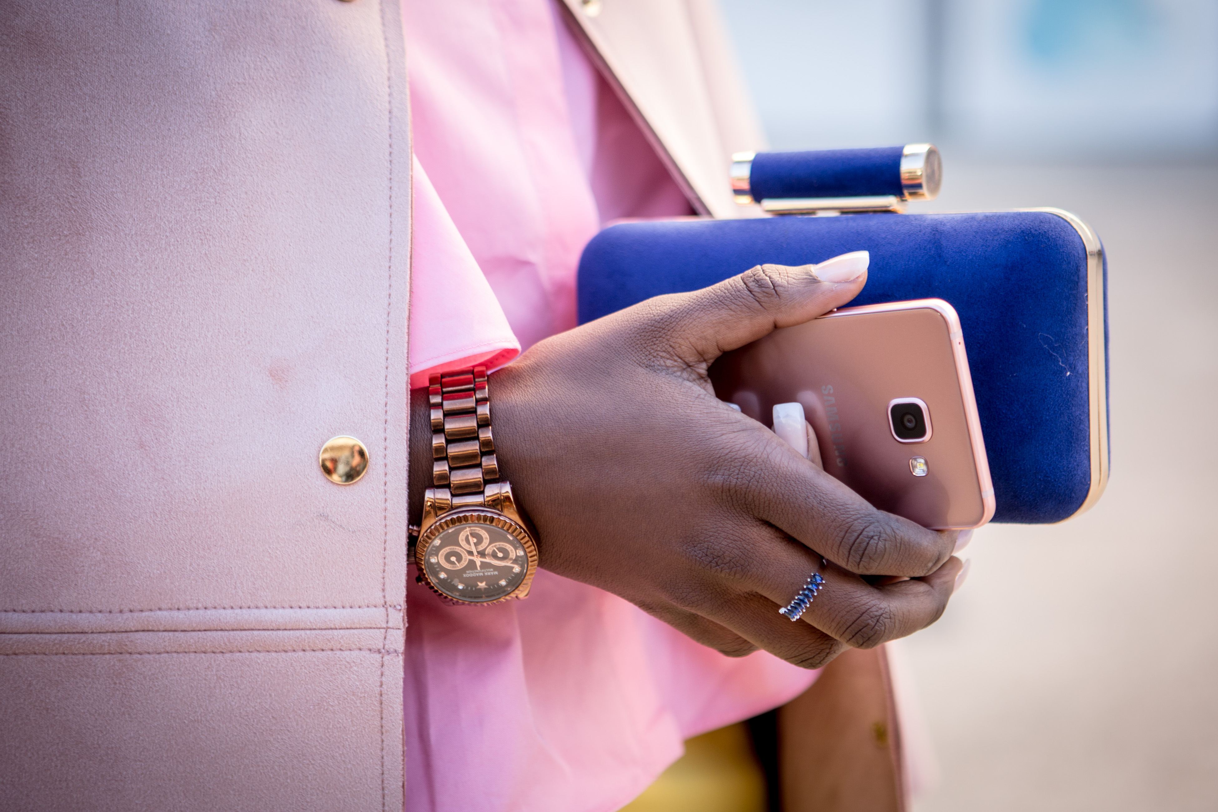 A close up of a woman wearing a pink jacket and a gold watch, carrying a rose gold smartphone and a blue purse.