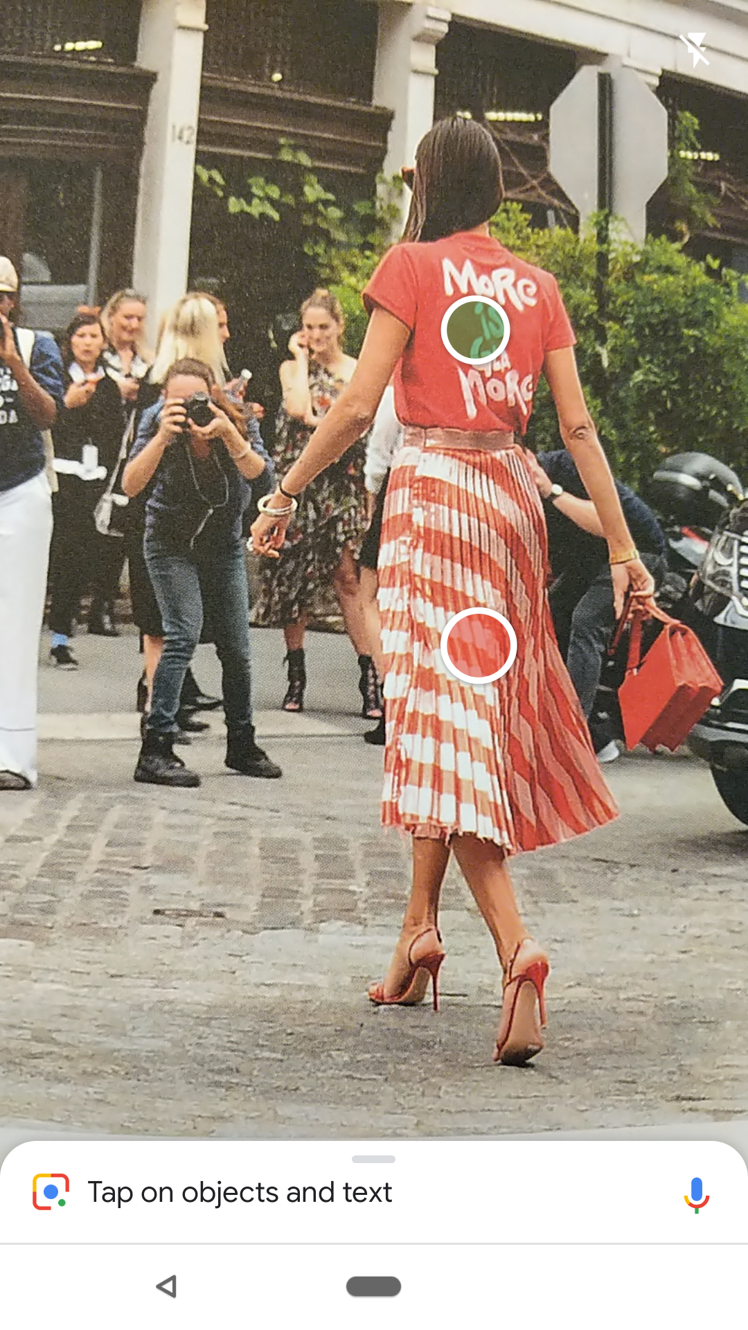 A woman walks down the street, with a green dot superimposed on her back.