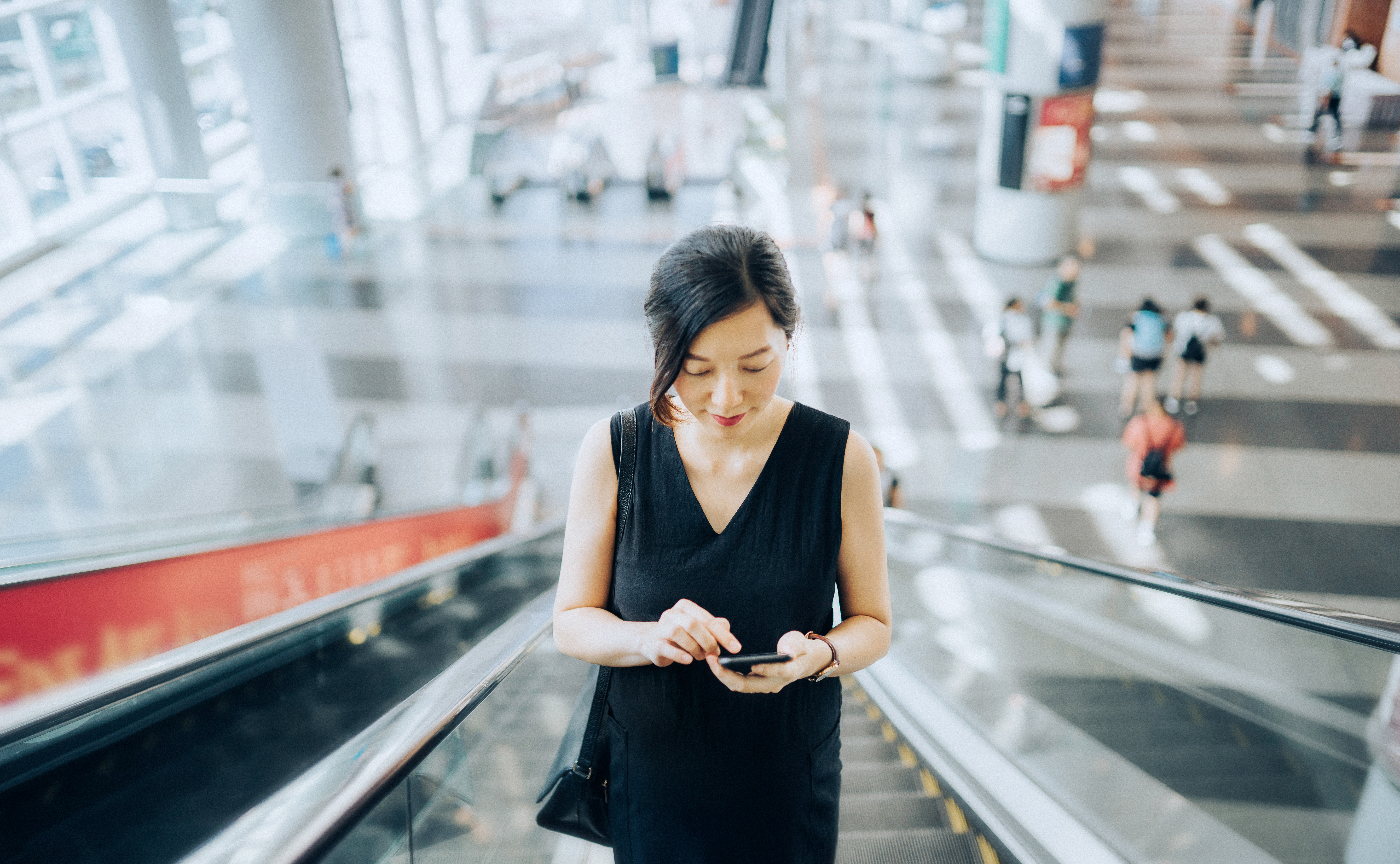 A young woman on an escalator looks at her phone.