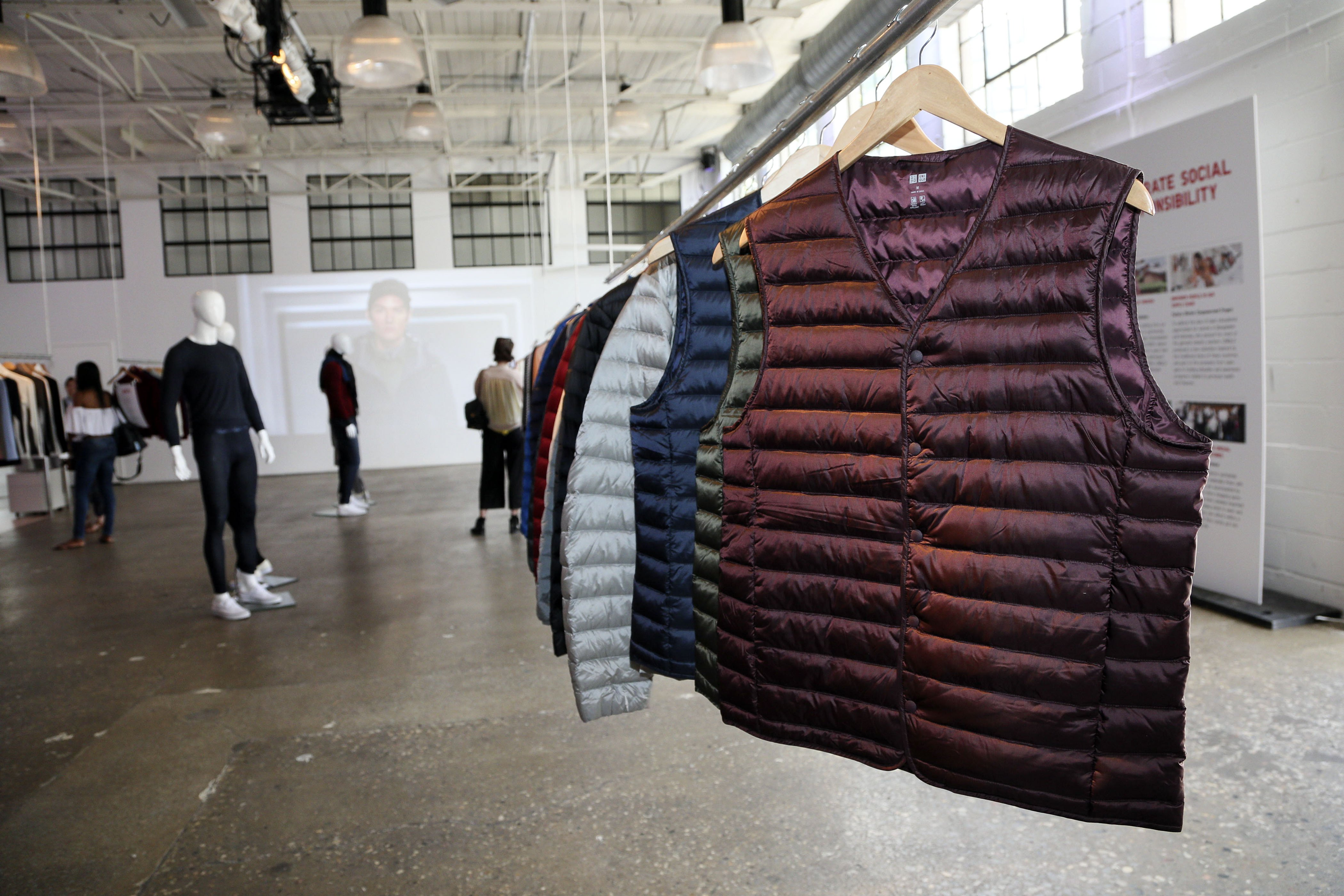 Uniqlo puffer vests hang on a rack.