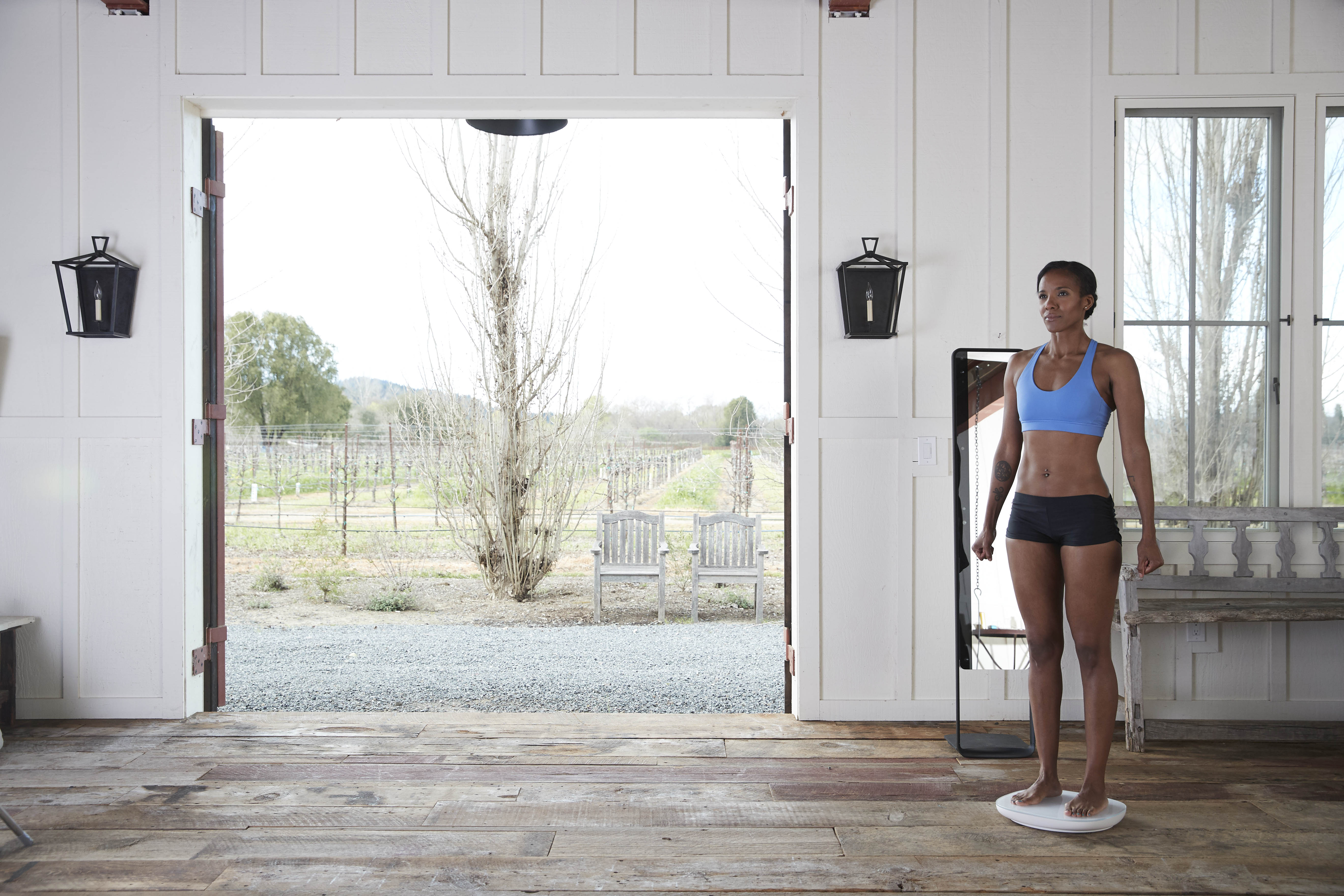 A model stands on the scale in a sports bra and shorts.