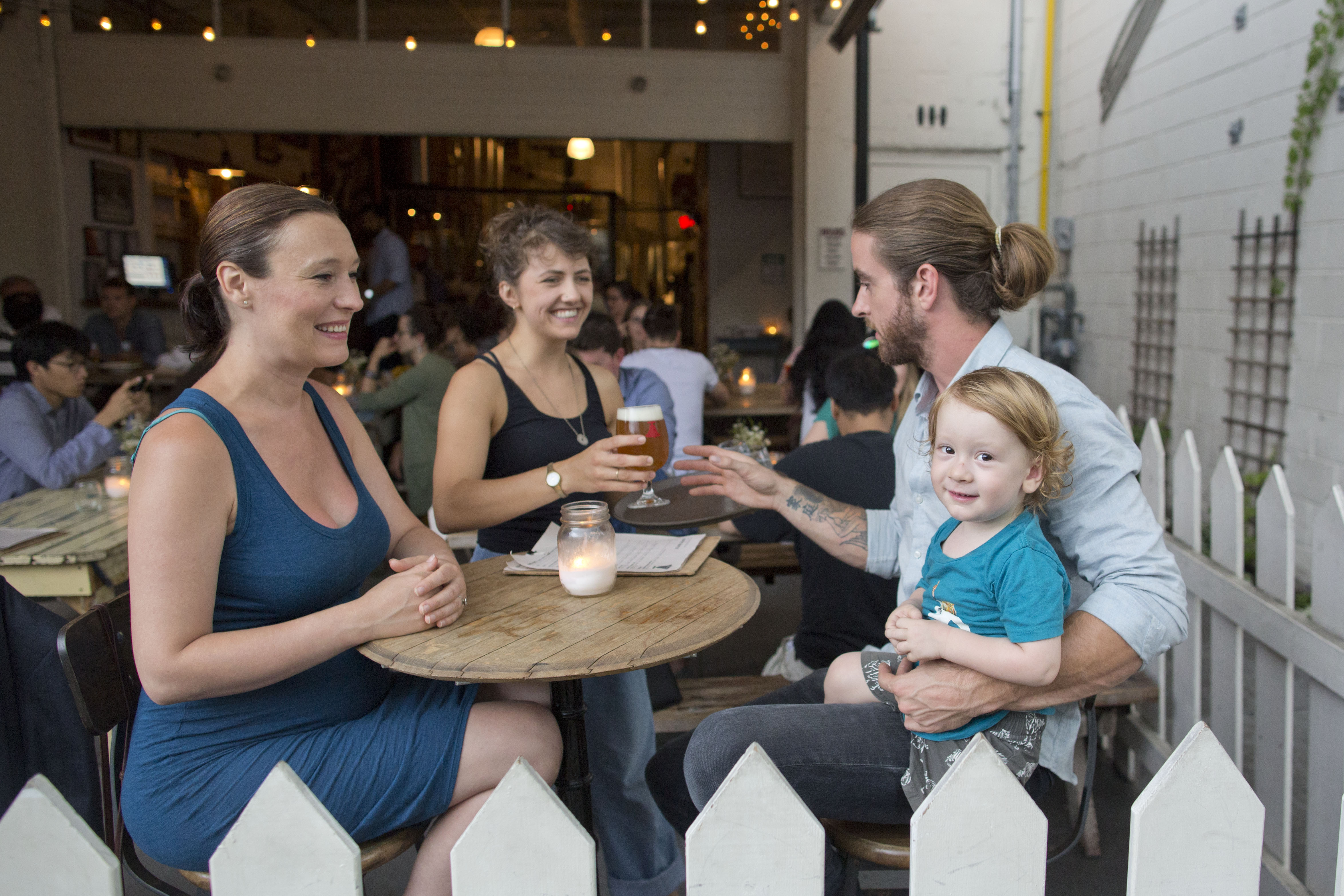 Three white young adults (two women, one man, with a man-bun)sitting at a bar outside, toasting to pints of beer, with a toddler sitting on the man's lap