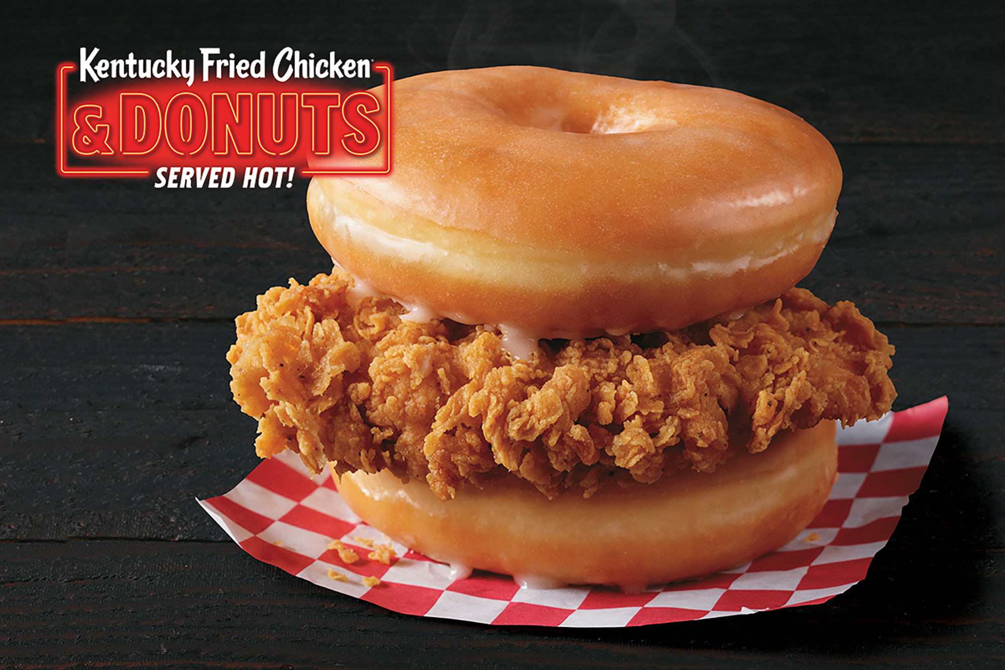A fried chicken filet between two doughnuts on a red-and-white checkered piece of paper.