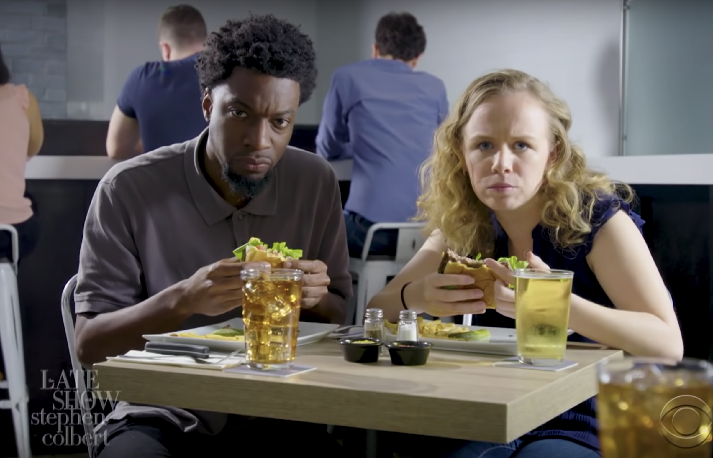 A man and a woman with cheeseburgers in hand, looking at the camera inside a trendy restaurant