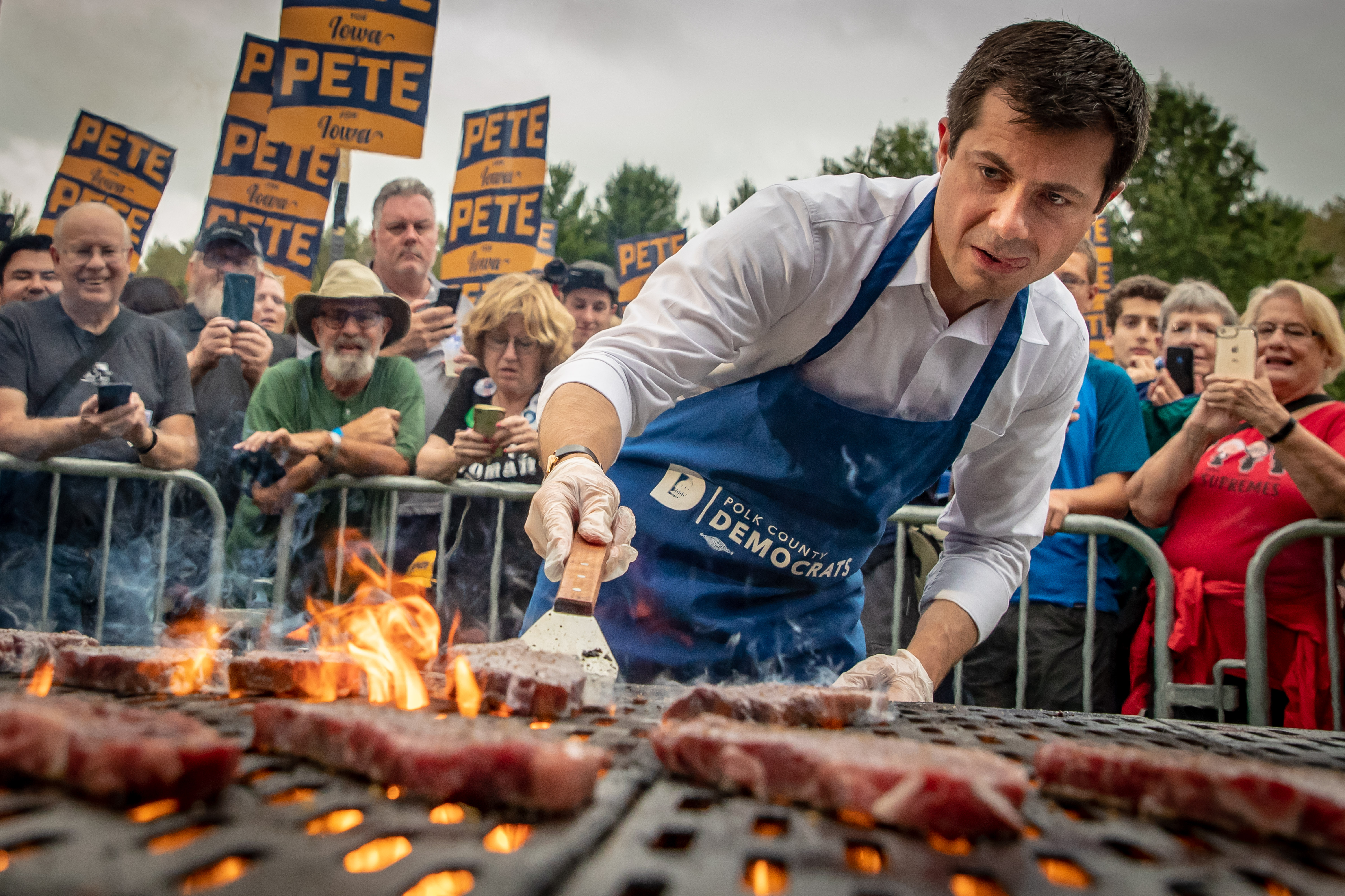 Pete Buttigieg grills a steak as supporters behind him hold signs and take photos.