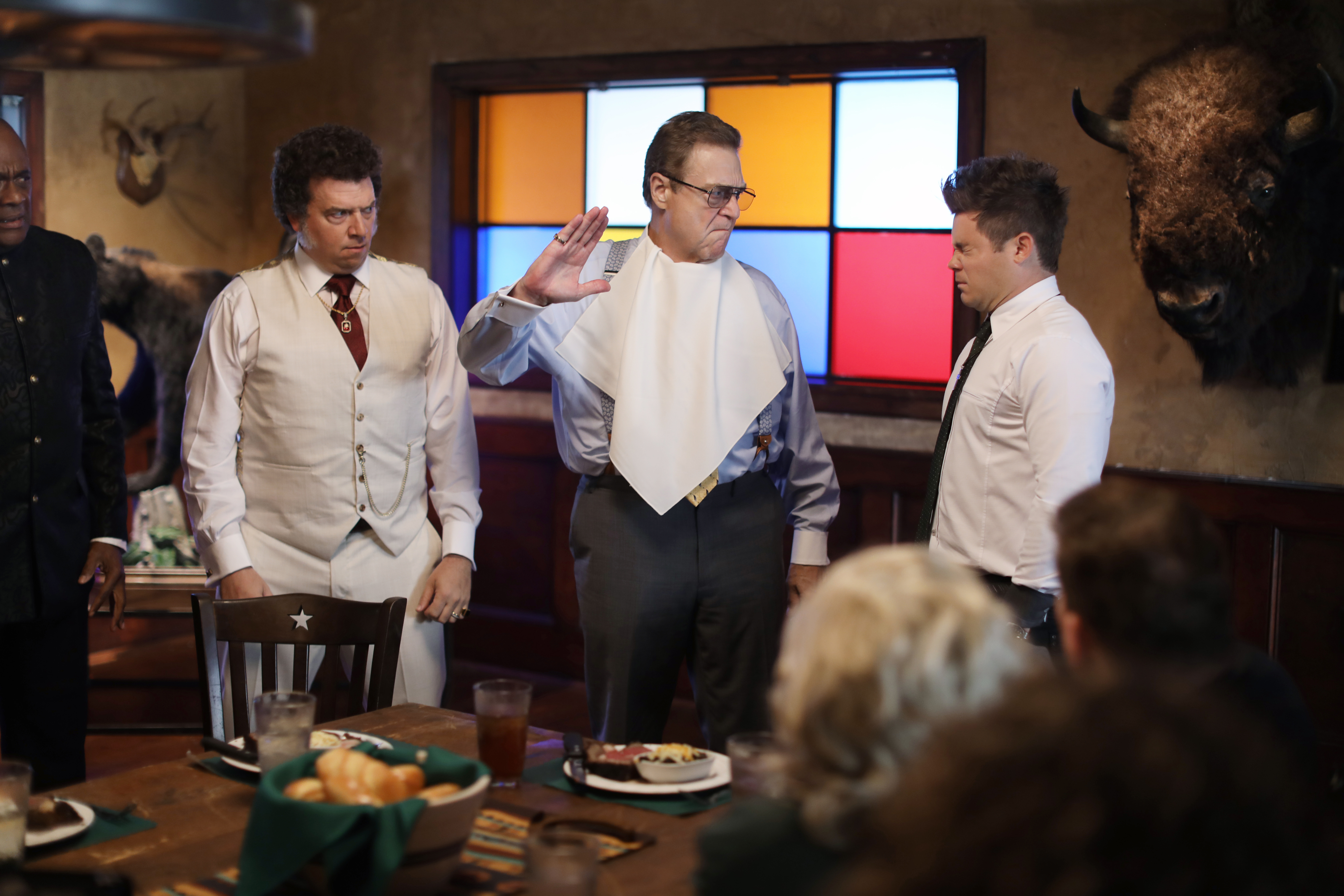 John Goodman with a napkin in his shirt, threatening to slap Adam DeVine, while Danny McBride stands on the left