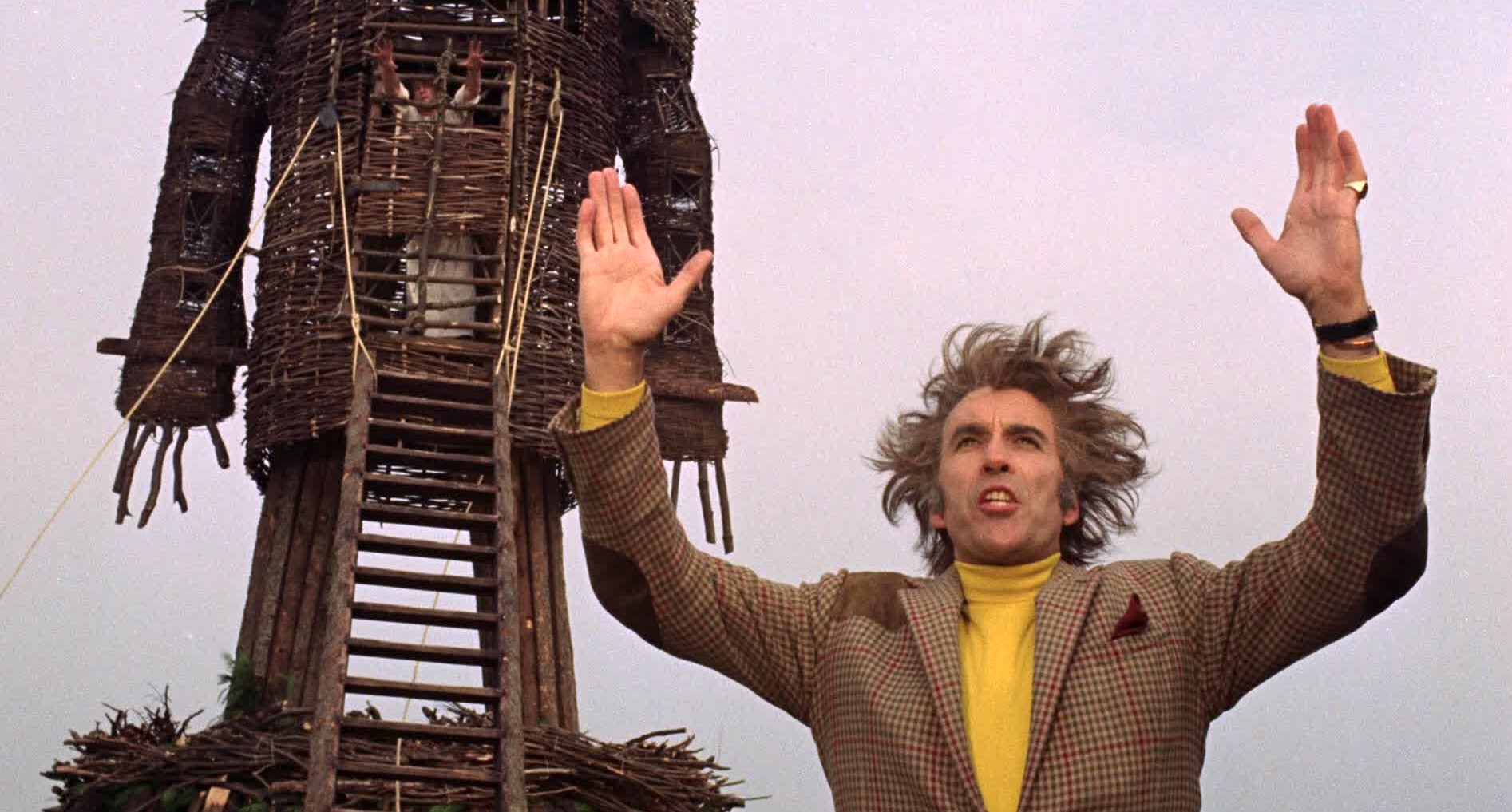 Lord Summerisle holds two hands in the air as he preaches to the crowd and prepares light the wicker man and Sgt. Neil Howie aflame
