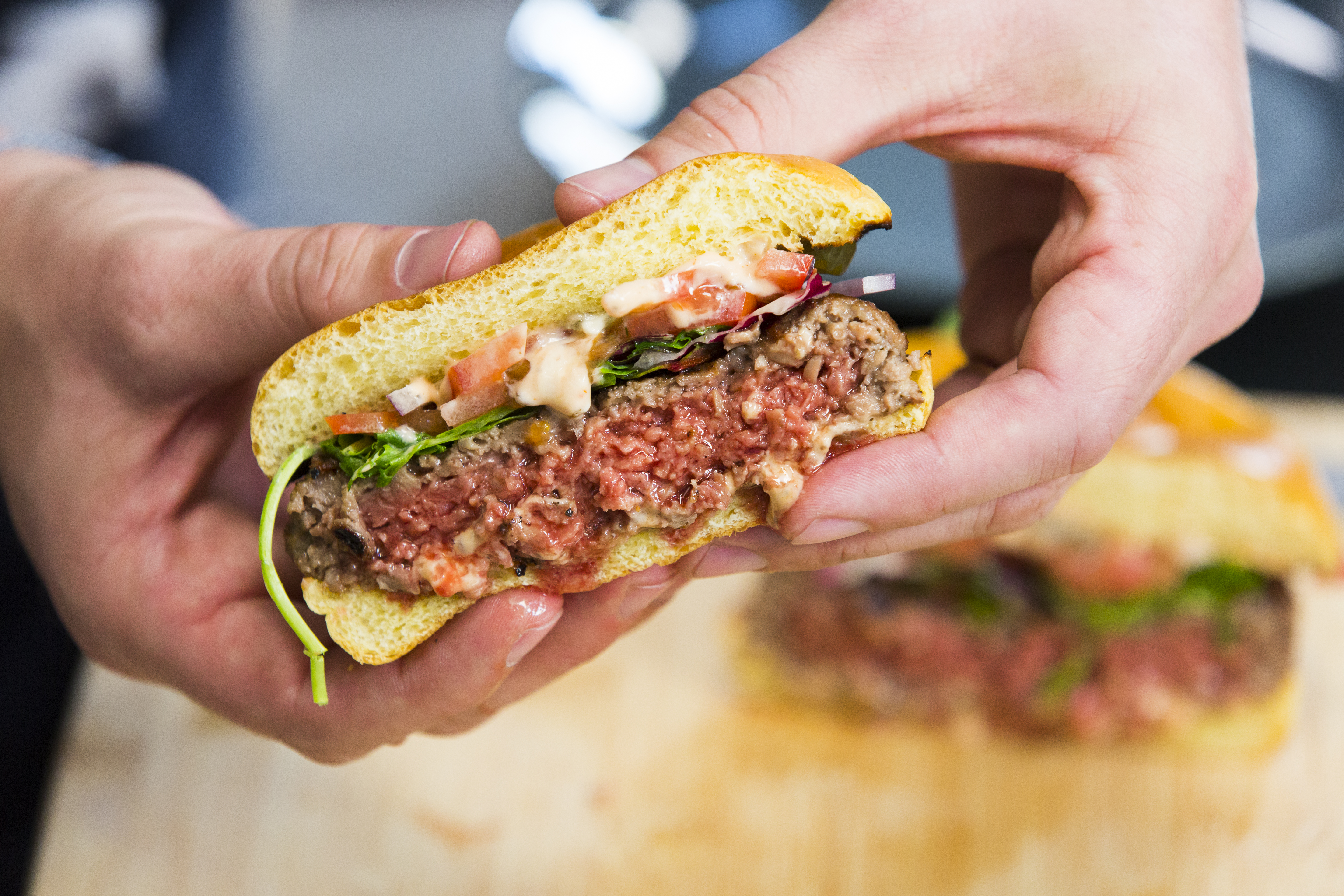 An Impossible burger cut half open and in a person's hands.