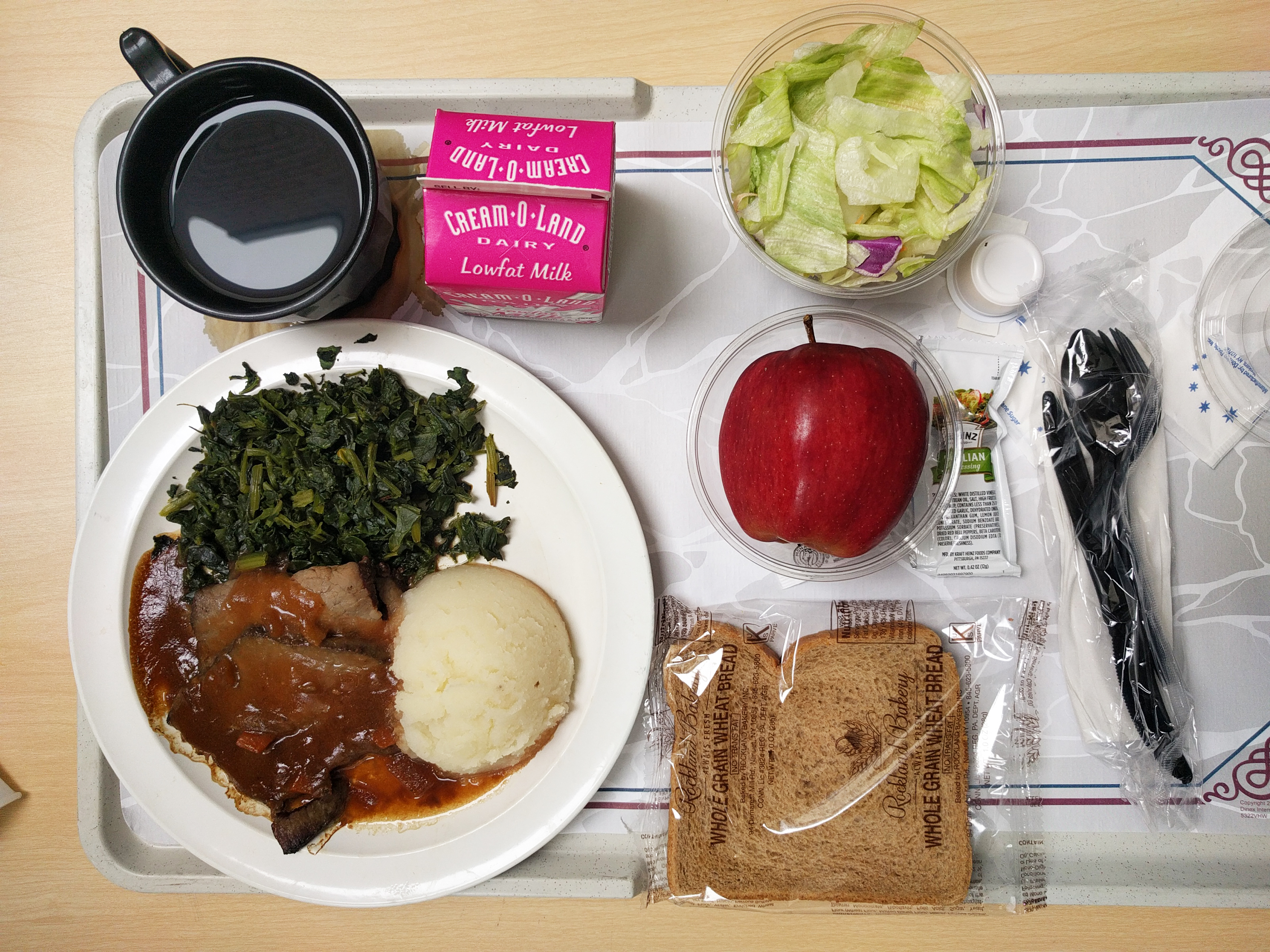 A plate of drab hospital food, including a plate of meet and potatoes, an apple, a carton of milk, a plastic-wrapped slice of whole wheat bread, and a plastic cup of coffee