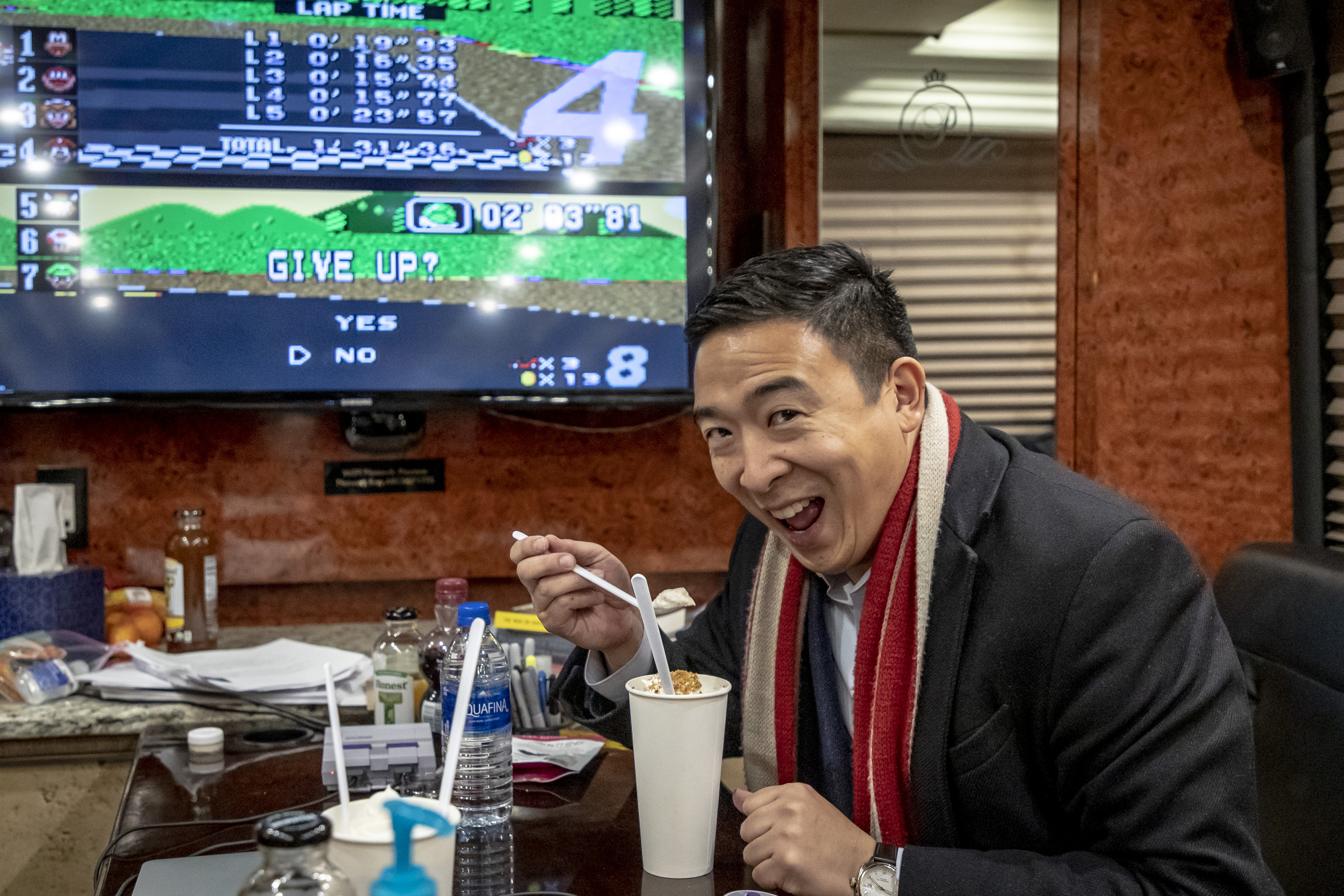 Man holds spoon containing ice cream up with his right hand, alongside a milkshake glass, TV on in the background.