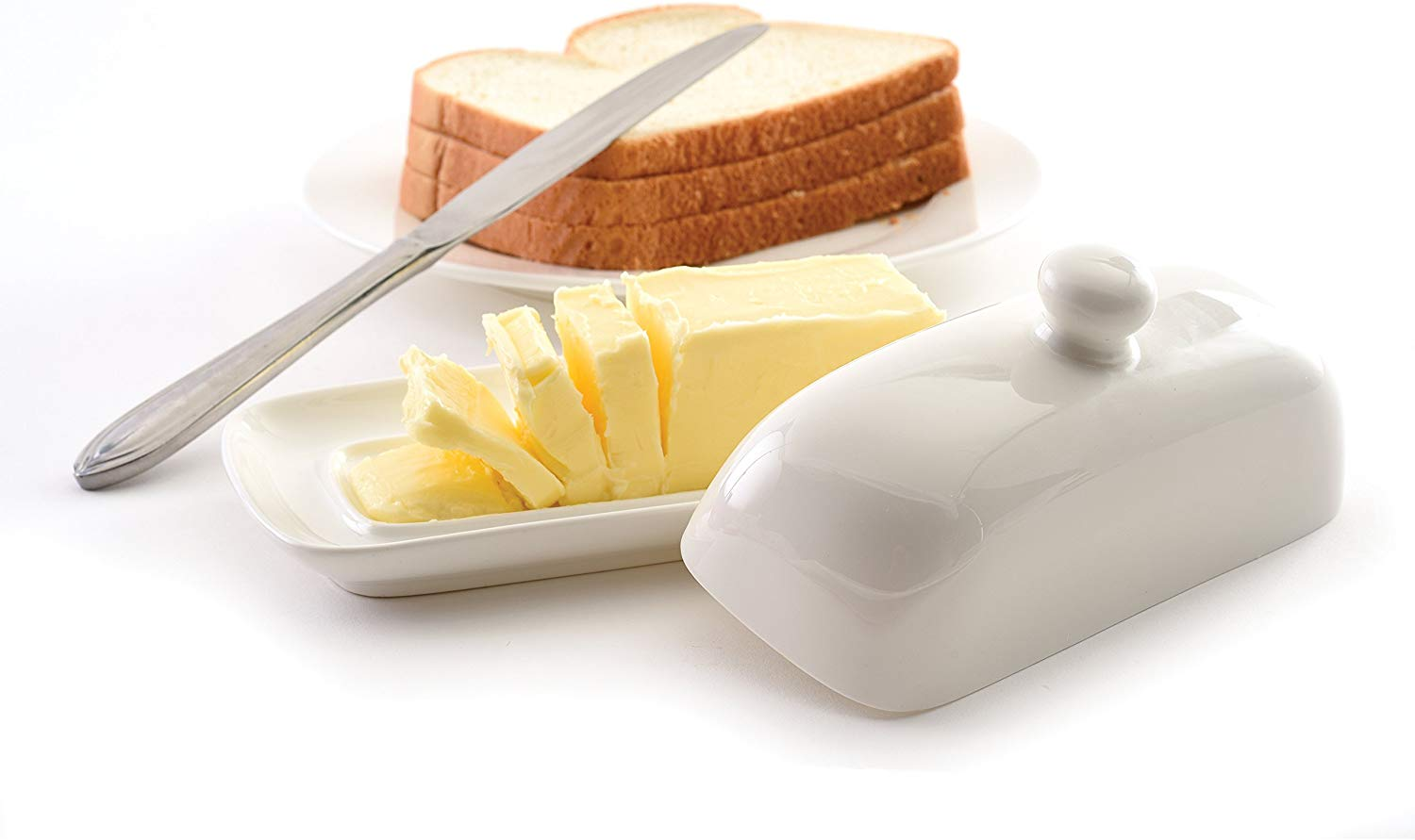 A butter dish containing a sliced stick of butter with a plate of bread in the background