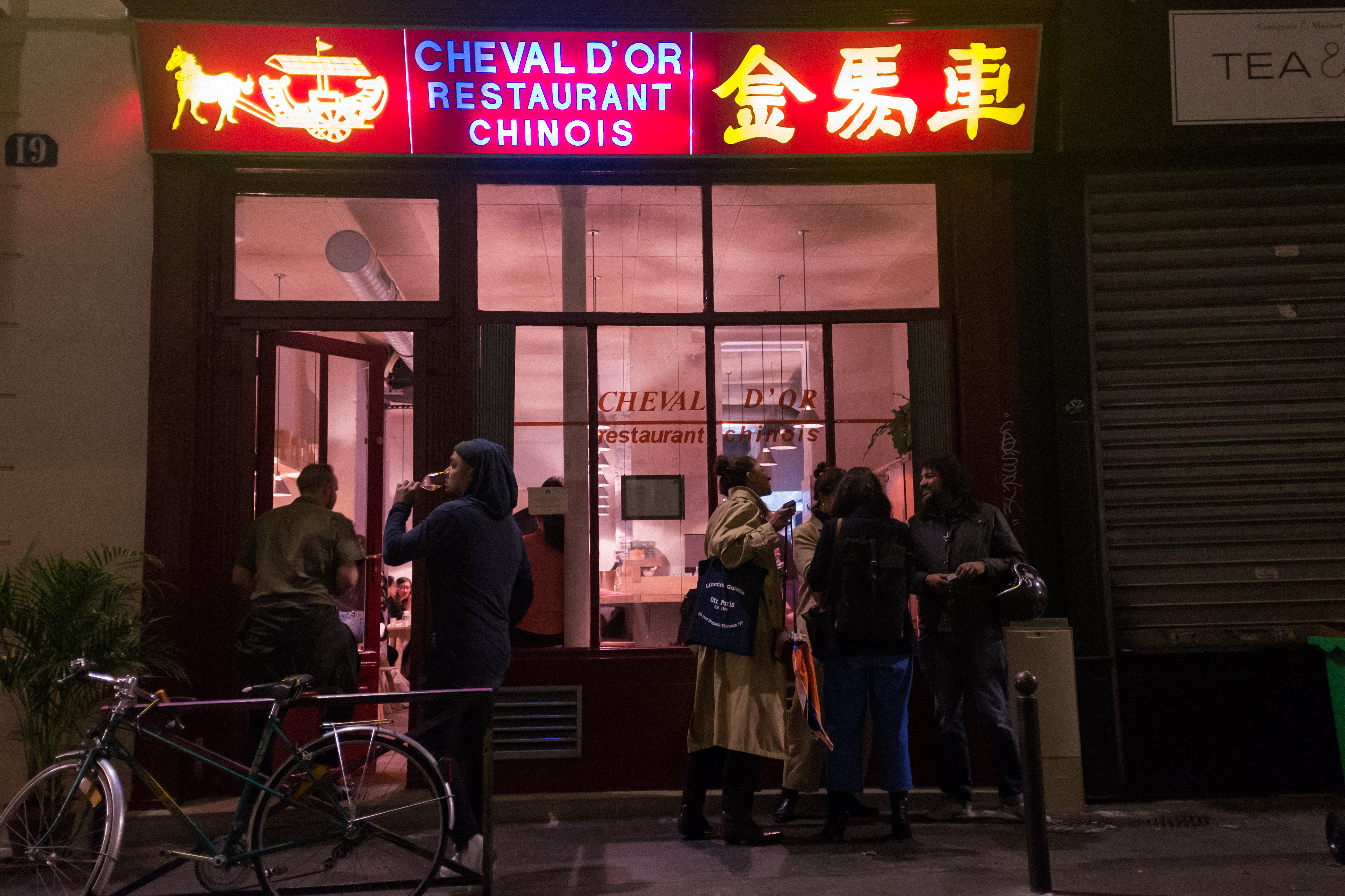 The exterior of a hip Paris restaurant at night, whose sign is from an old-school Chinese restaurant