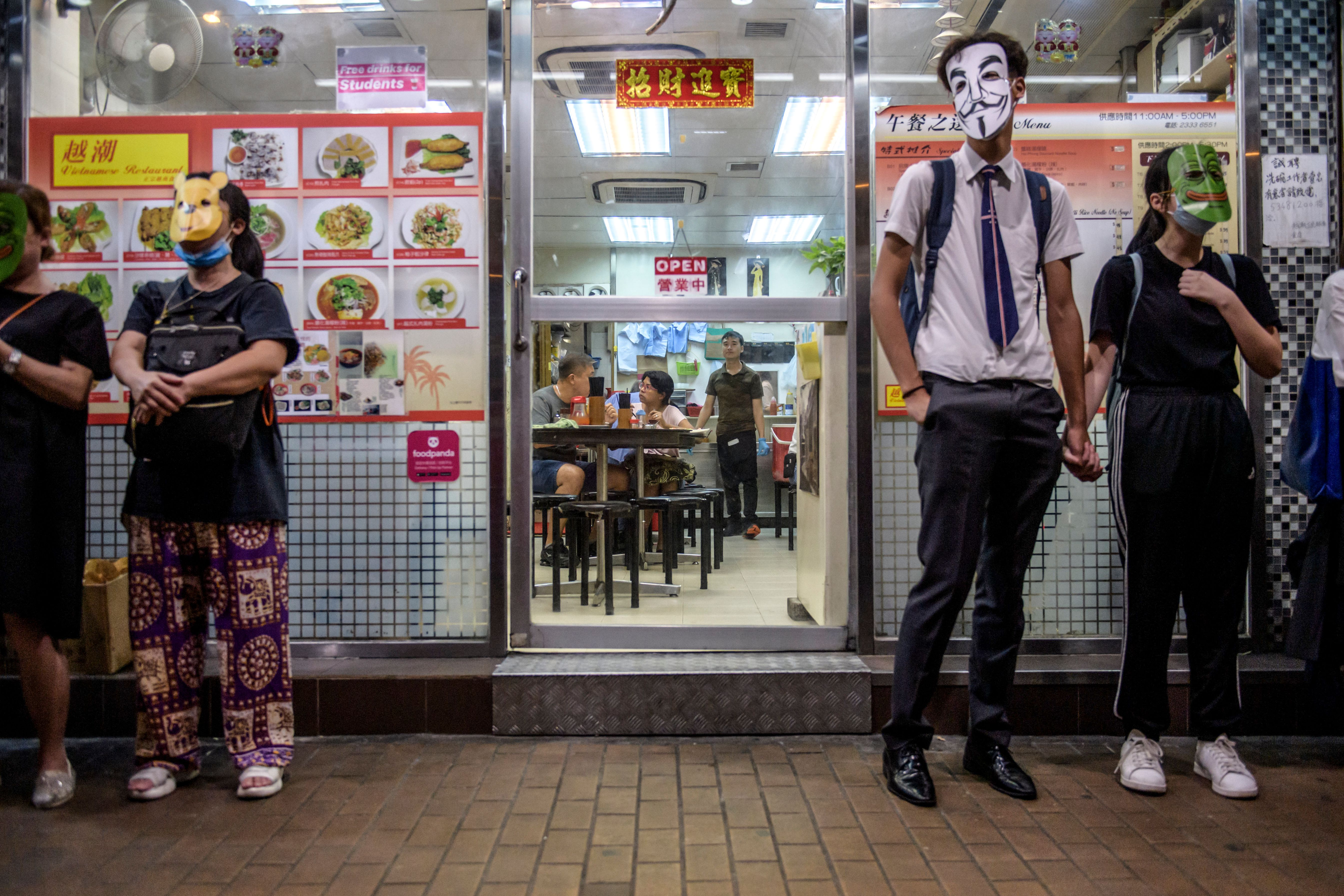 Masked protesters stand outside a restaurant