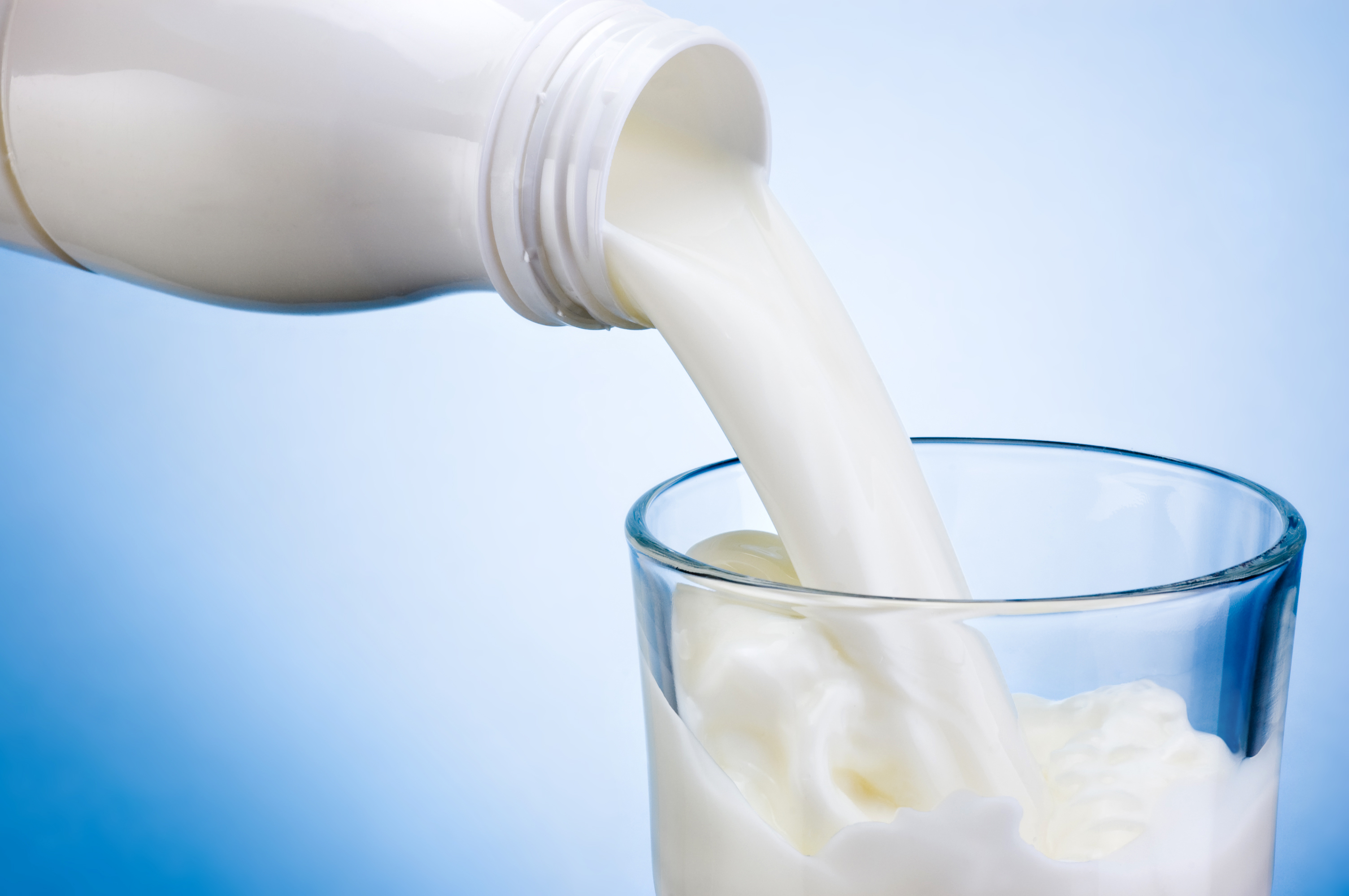 Milk pouring from a glass bottle into a glass cup.