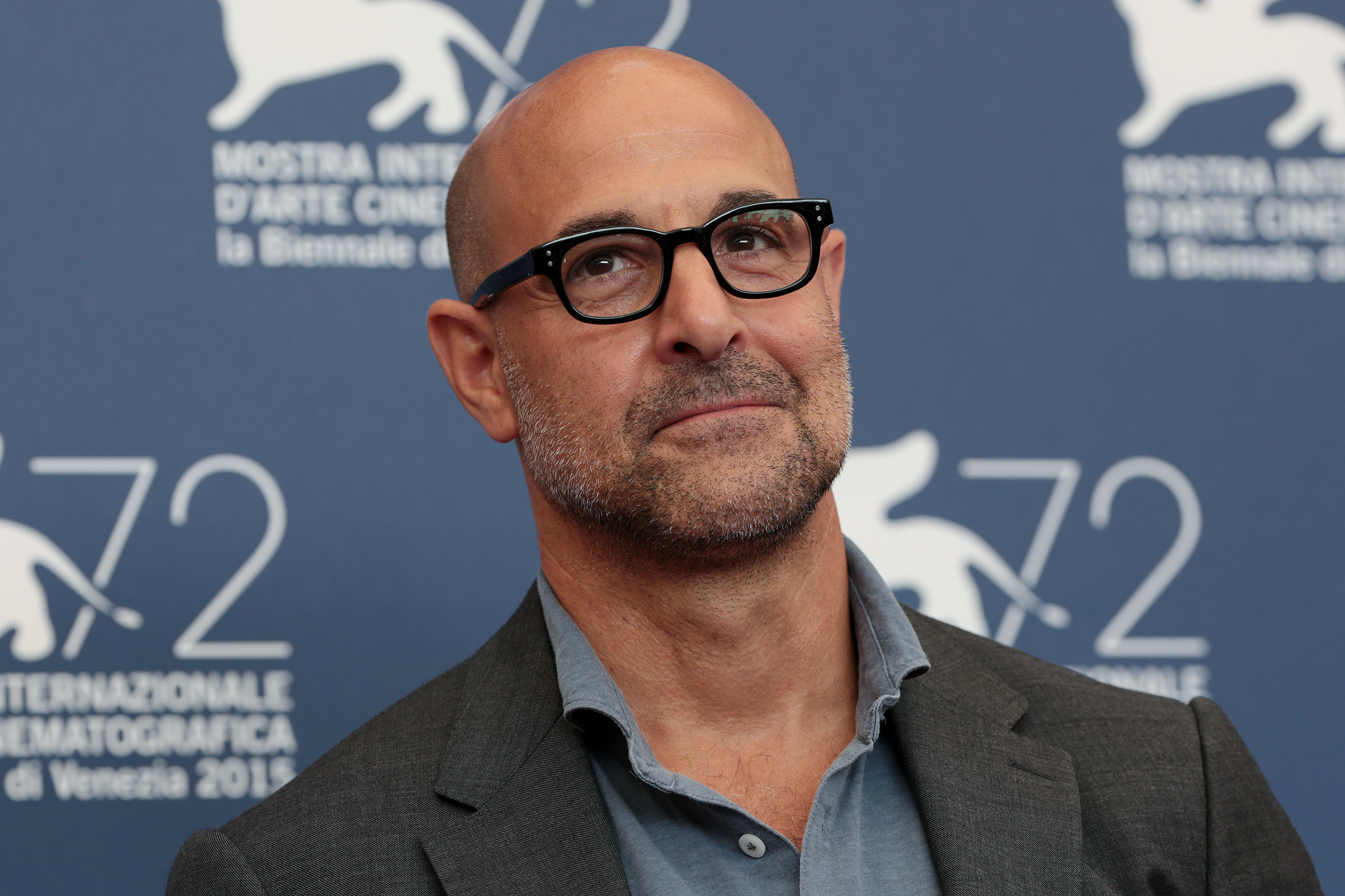 Stanley Tucci wearing glasses, a collared shirt, and a suit jacket.