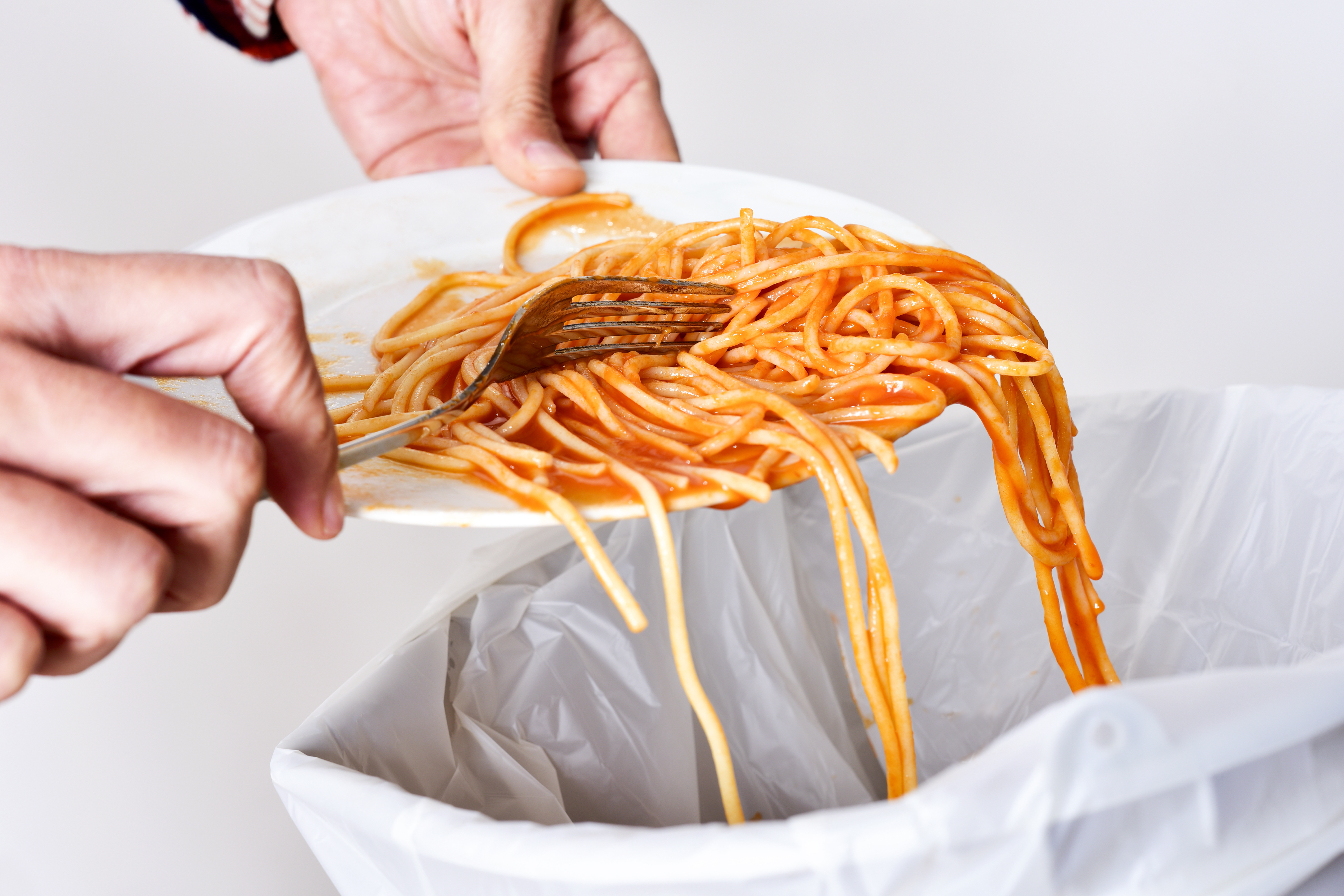Hands scraping a plate of spaghetti into the trash.