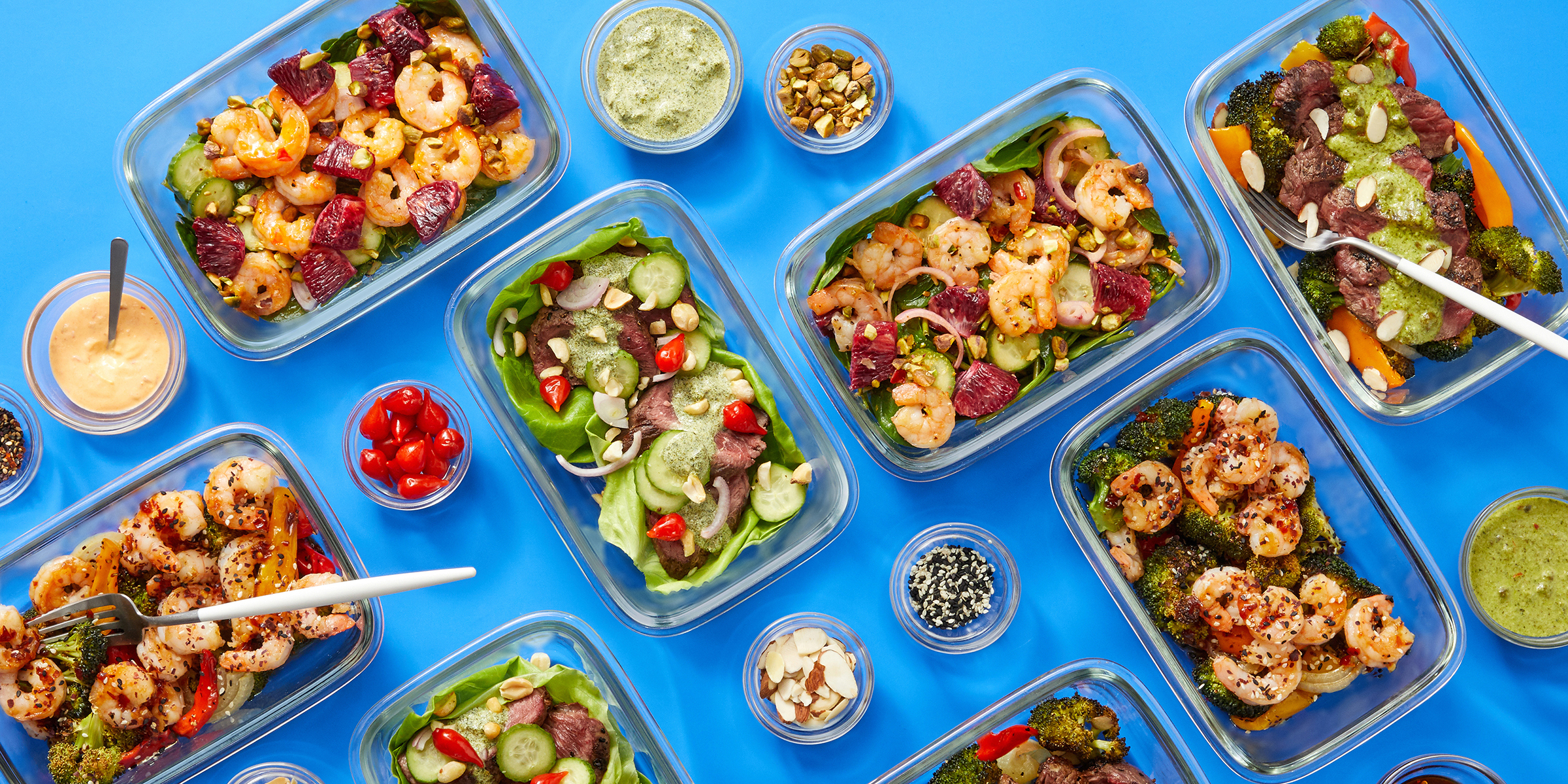 A spread of meal prep —glass containers filled with pre-portioned meals —on a blue background.