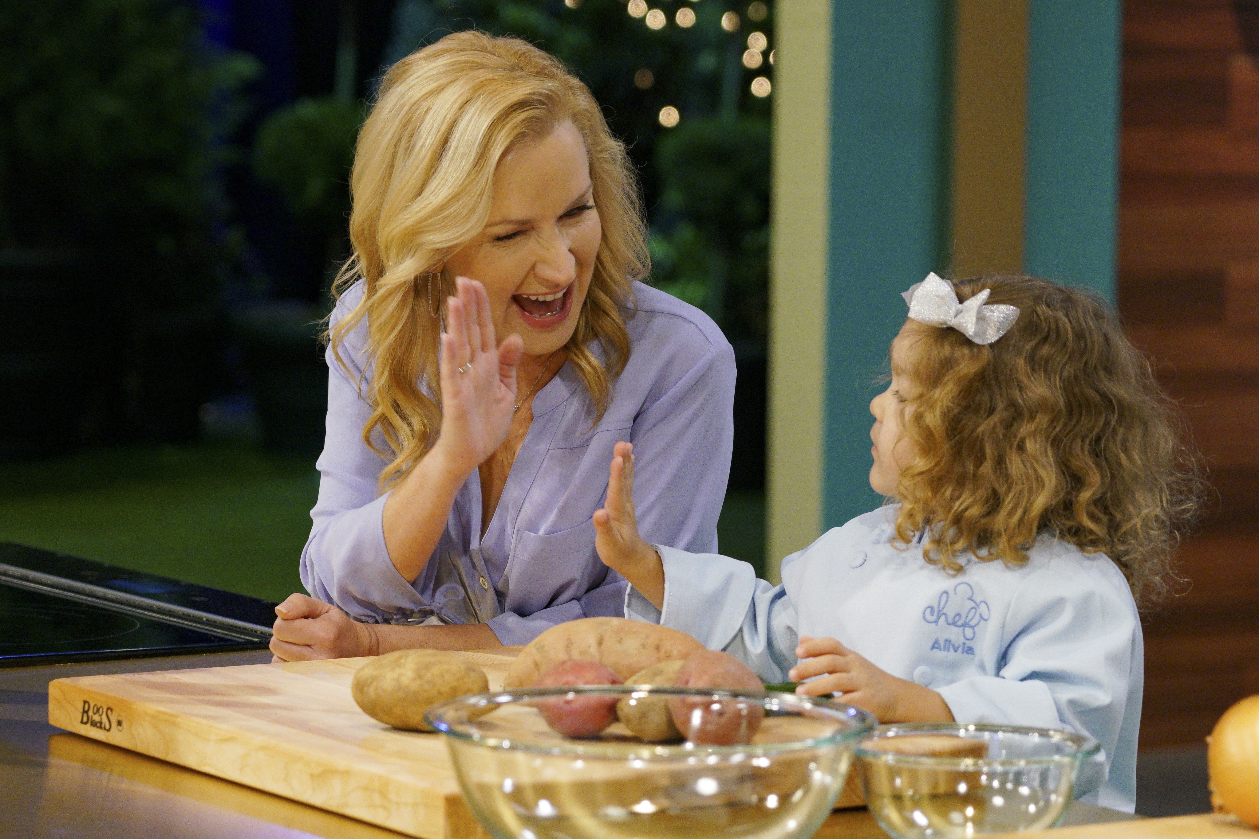 Angela Kinsey high-fiving a small child.